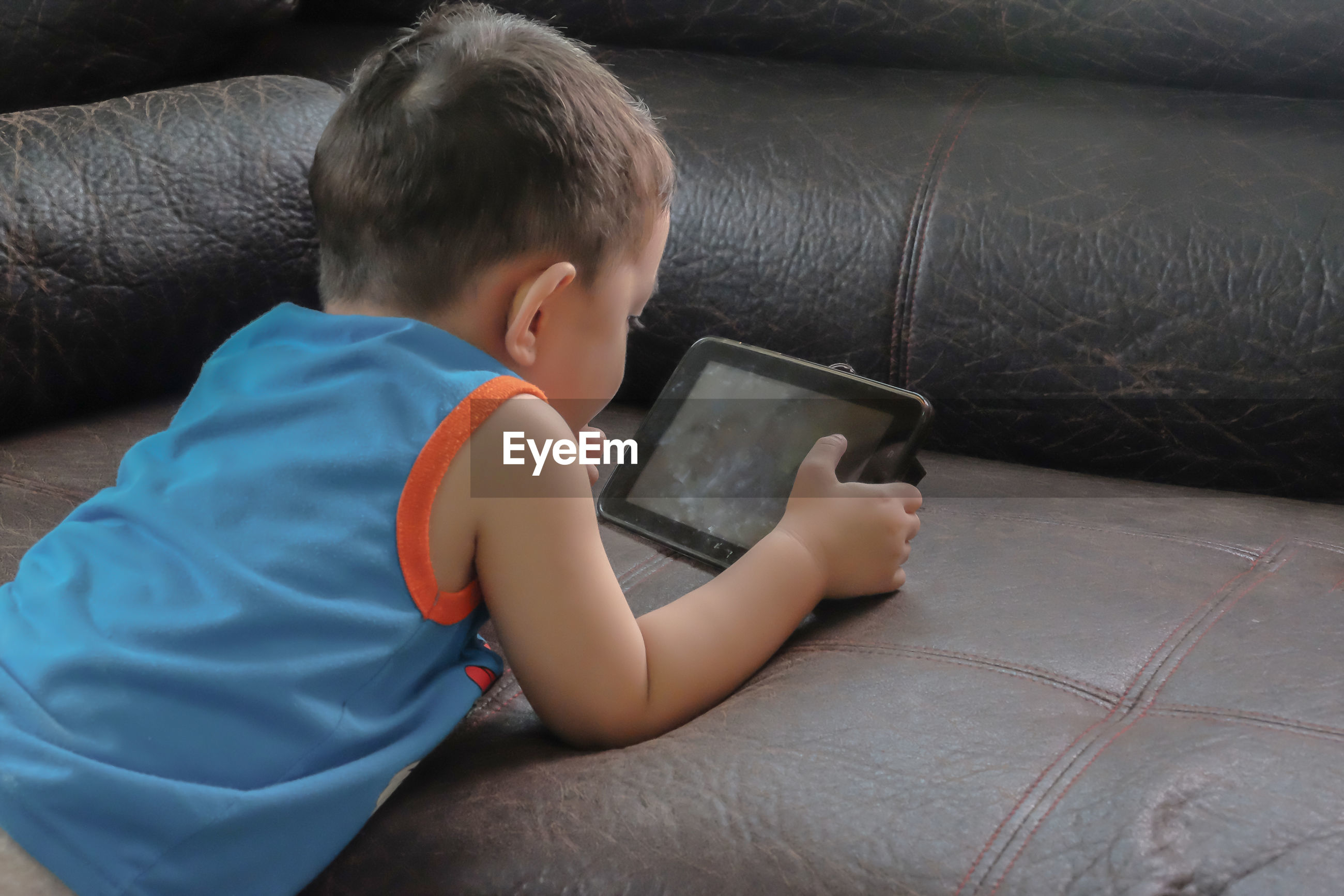 Boy watching video in digital tablet at home
