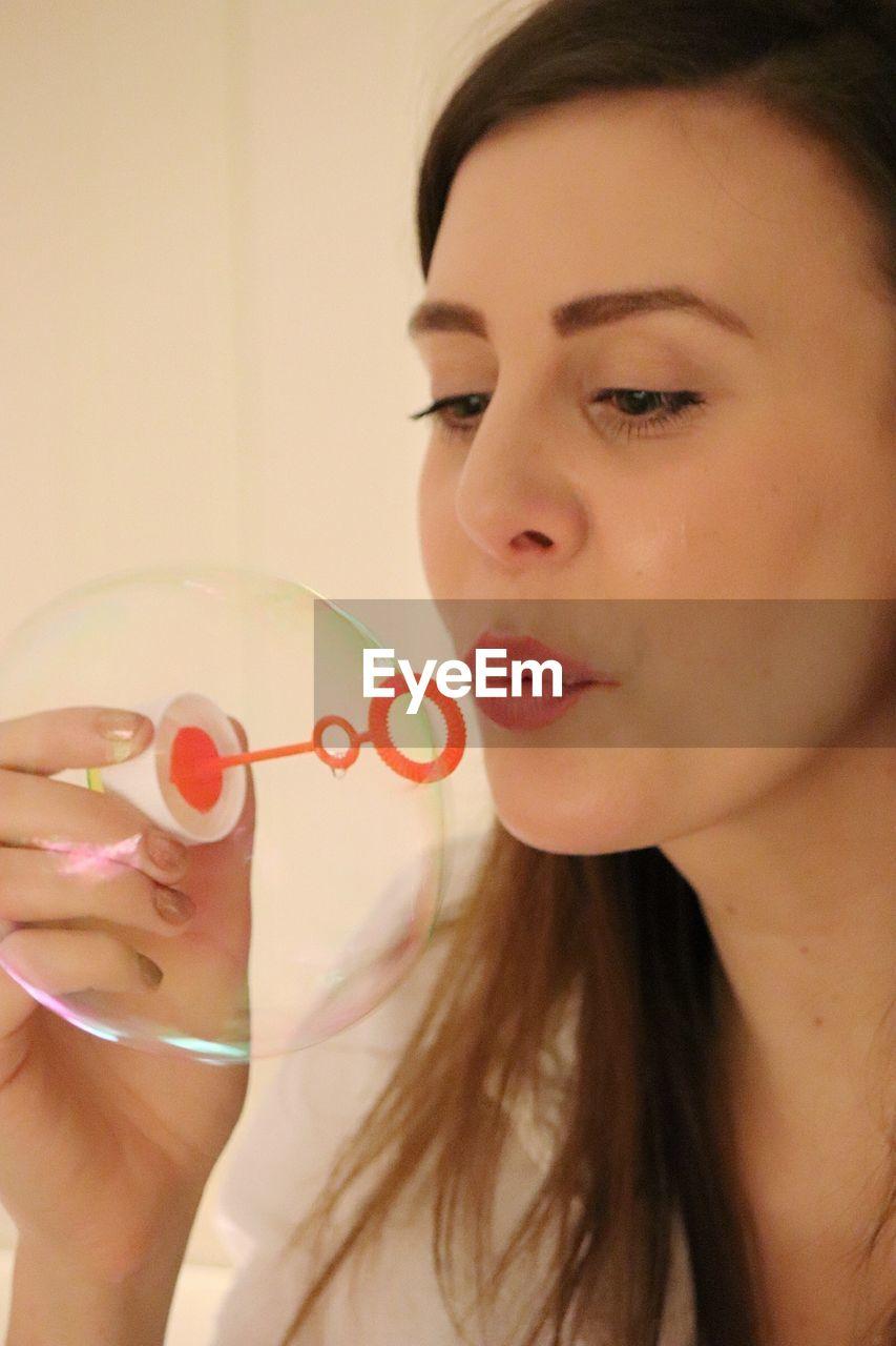 Close-Up Of Beautiful Woman Blowing Bubble