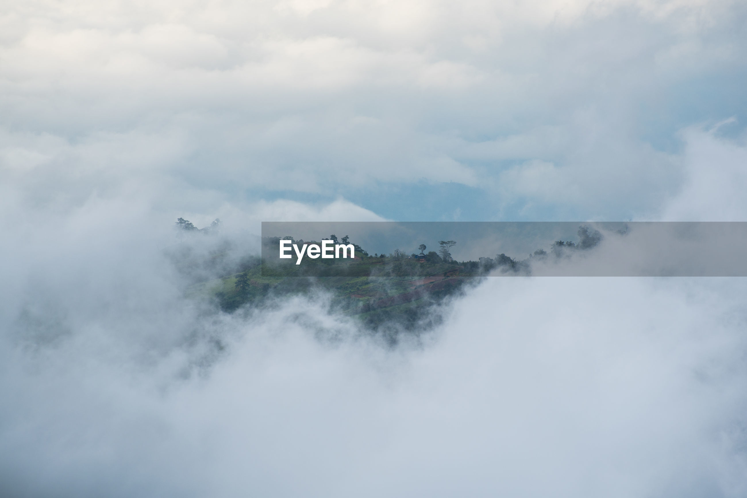 Clouds covering mountains against sky