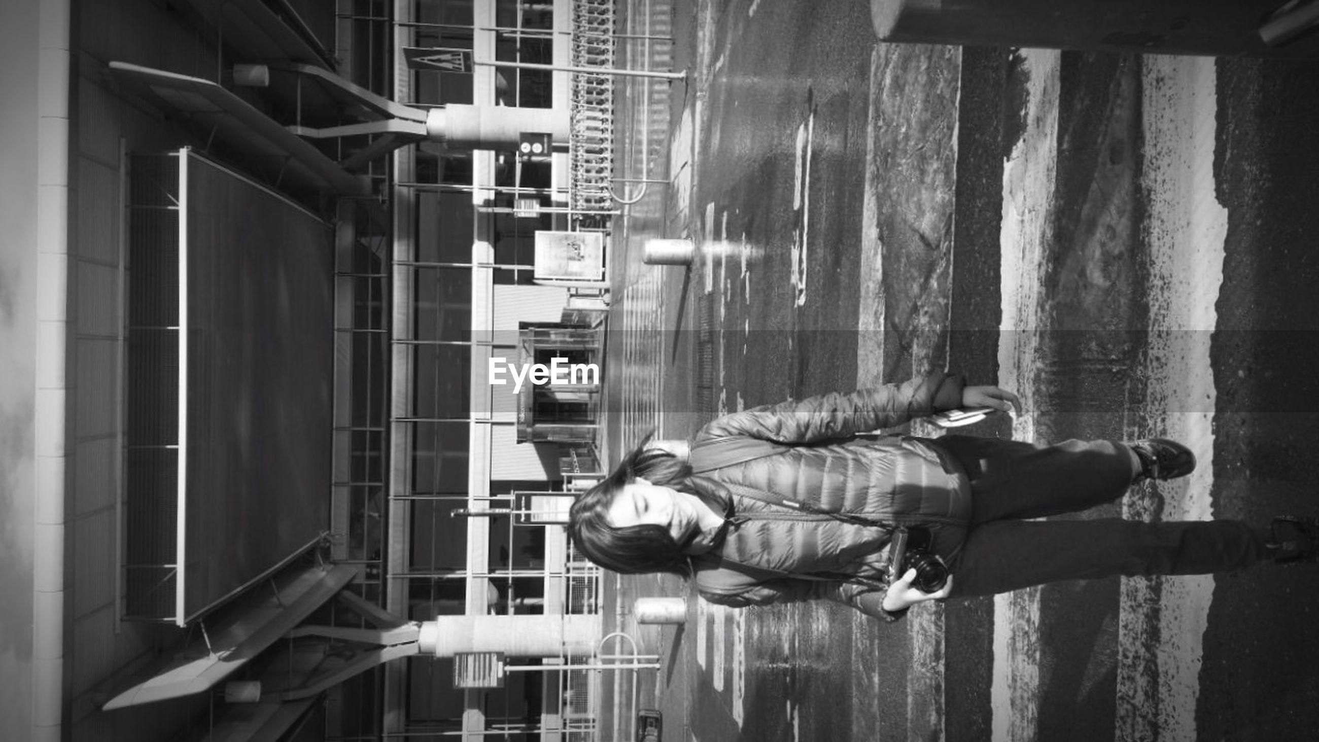 WOMAN STANDING ON FOOTBRIDGE