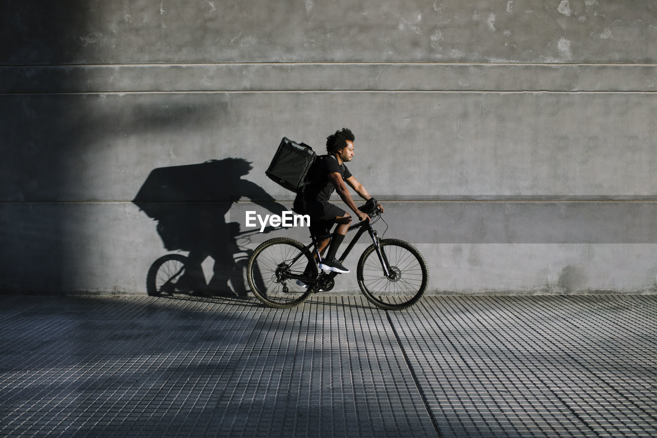 SIDE VIEW OF MAN RIDING BICYCLE AGAINST CITY