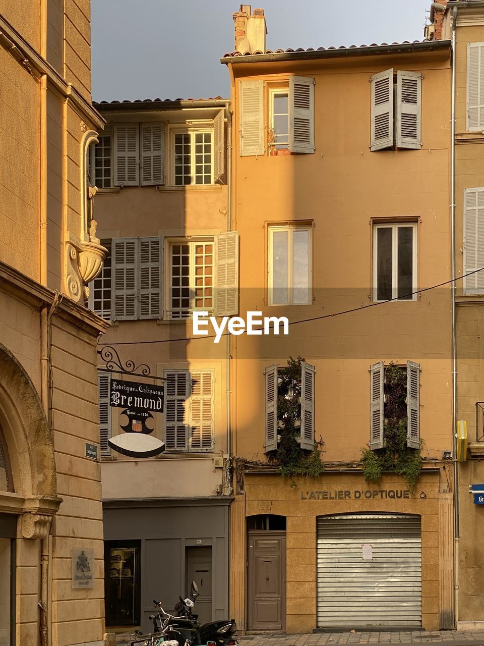 building exterior, architecture, built structure, window, building, city, residential district, day, no people, outdoors, sunlight, balcony, nature, street, communication, yellow, shadow, lighting equipment, city life, apartment