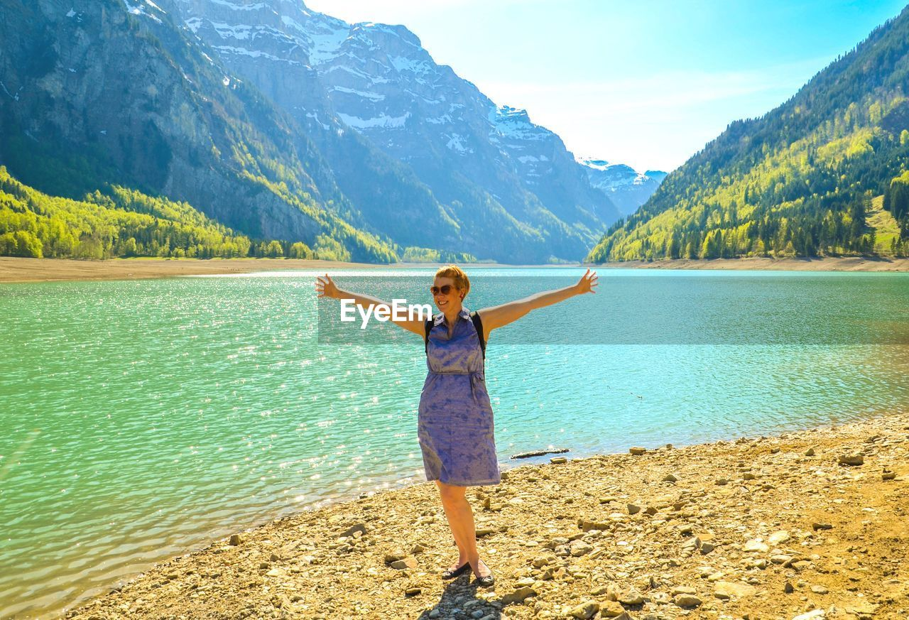 Happy mid adult woman wearing sunglasses standing at lakeshore against mountain during sunny day