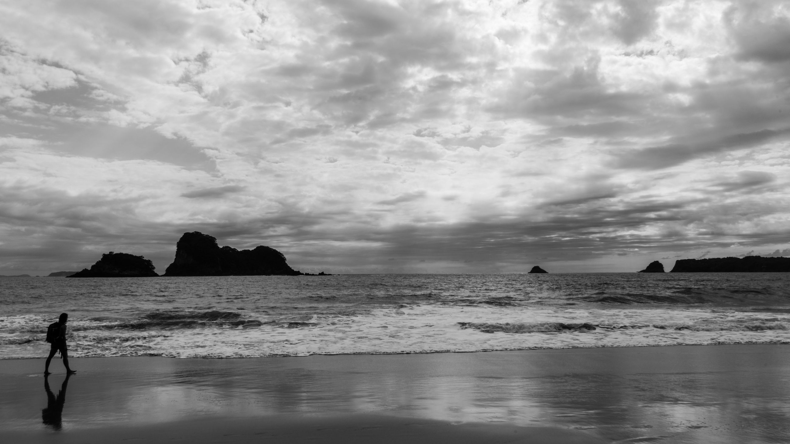 Silhouette man walking on beach against sky at dusk