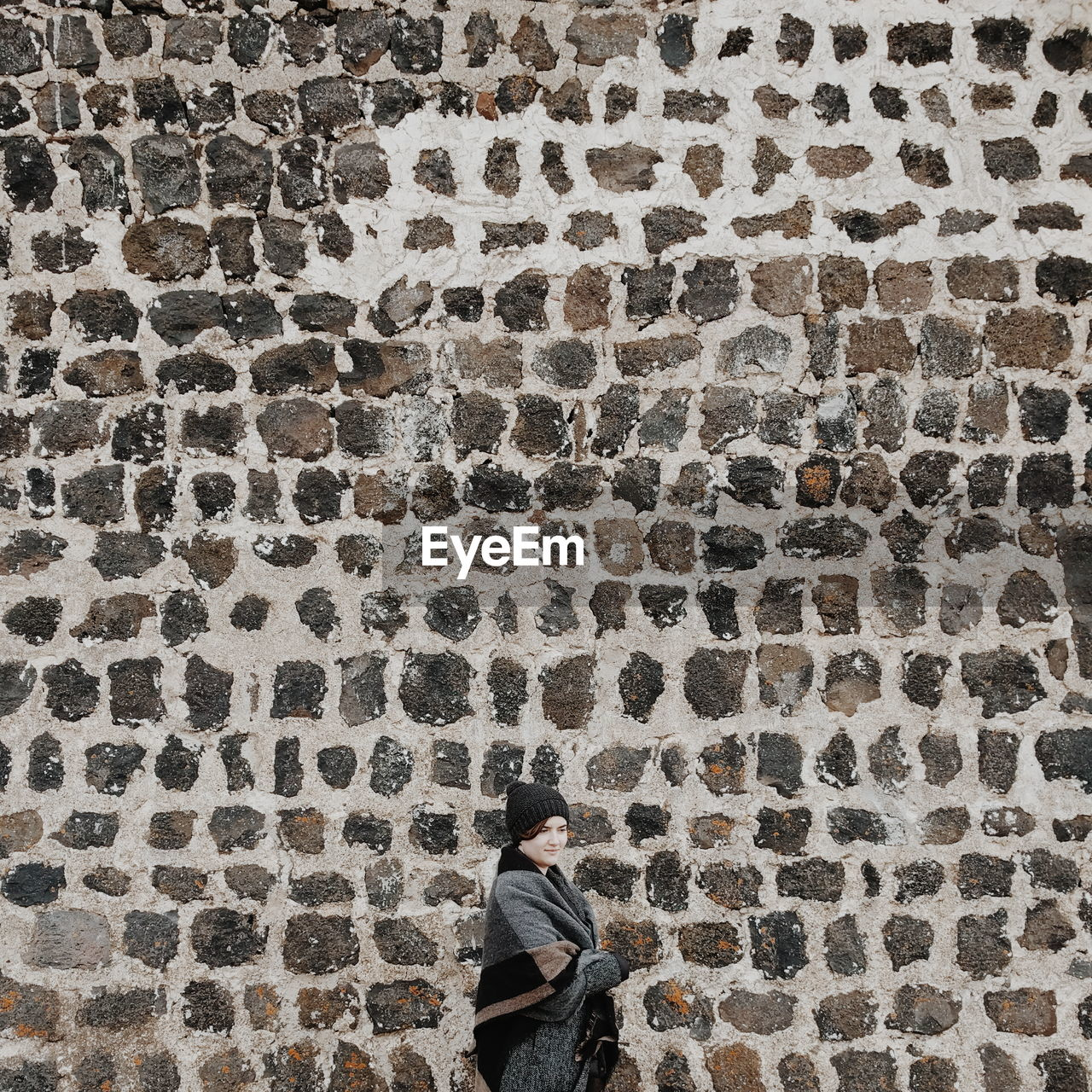 Young Woman In Front Of Stone Wall
