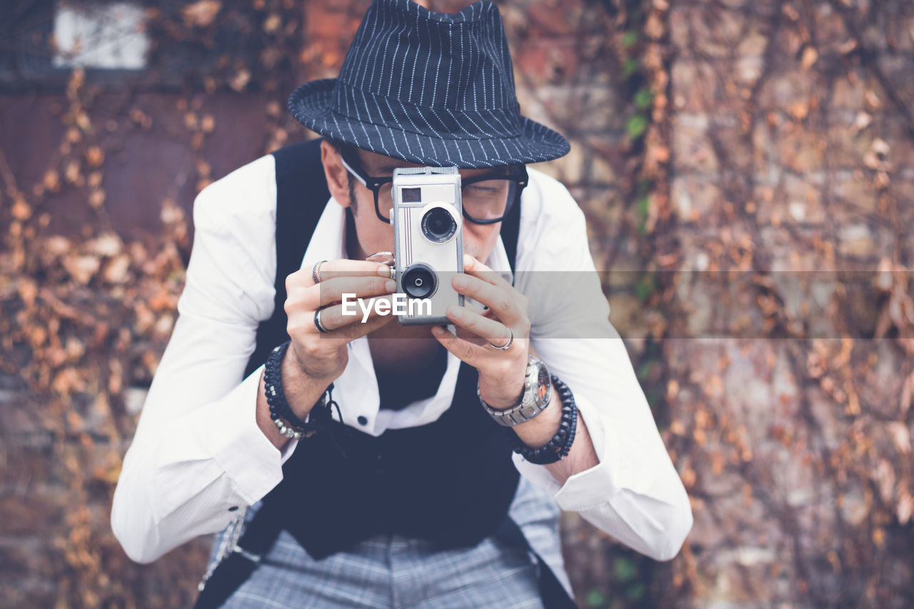 Mature man photographing while standing against brick wall during autumn