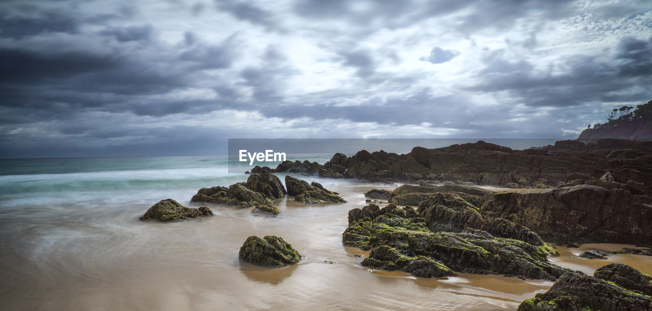 Rock Formations At Seashore Against Cloudy Sky
