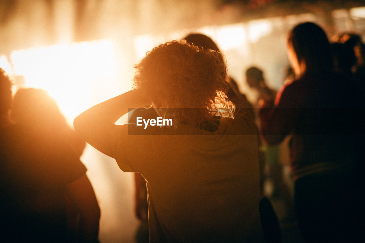 real people, night, indoors, focus on foreground, enjoyment, fun, illuminated, performance, arts culture and entertainment, large group of people, leisure activity, nightlife, togetherness, men, lifestyles, women, excitement, crowd, audience, popular music concert, adult, people