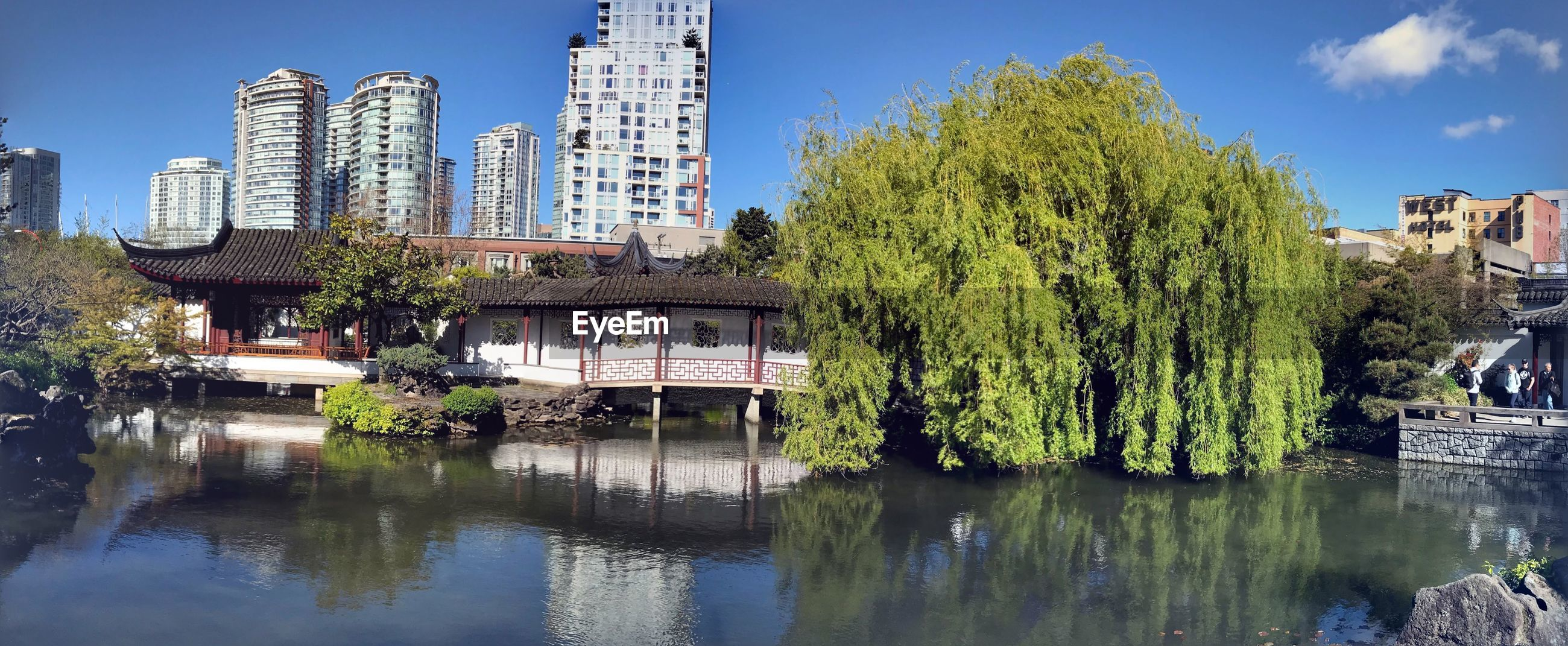 SCENIC VIEW OF LAKE BY TREES AGAINST BUILDINGS