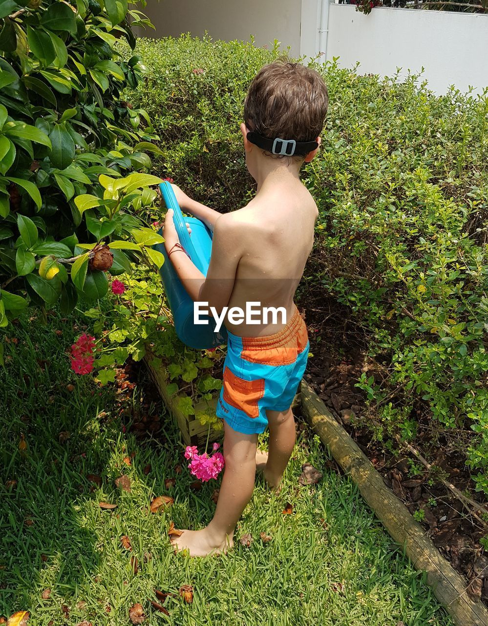 BOY PLAYING IN WATER AT YARD