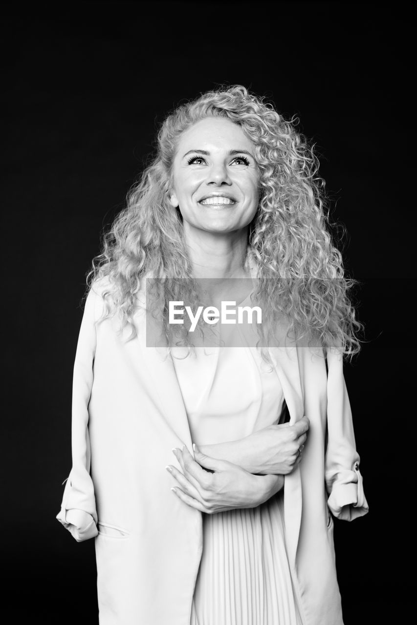 Smiling woman with curly hair standing against black background