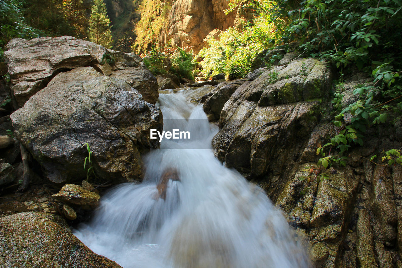 The rapid flow of the river between huge stones in the rocky mountains in summer,behind the sunlight
