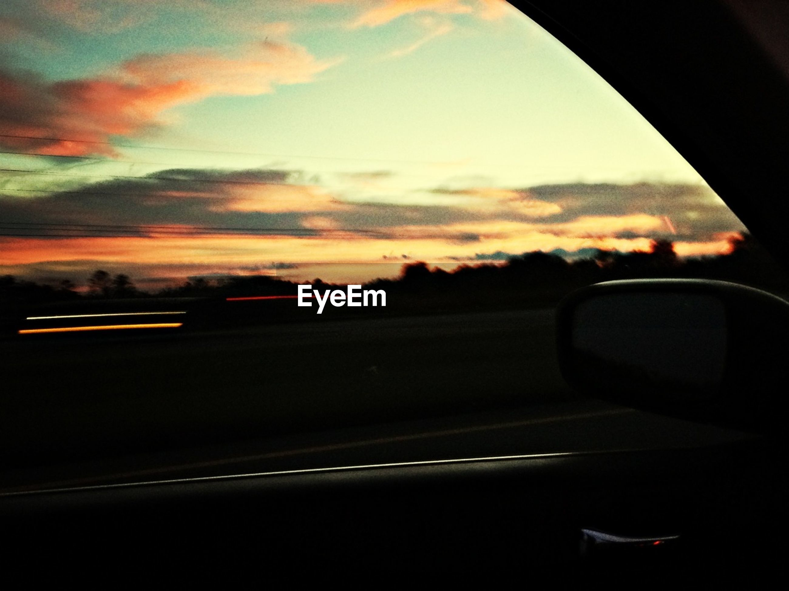transportation, car, mode of transport, land vehicle, sunset, vehicle interior, car interior, sky, windshield, glass - material, transparent, road, side-view mirror, travel, silhouette, window, part of, road trip, reflection, orange color