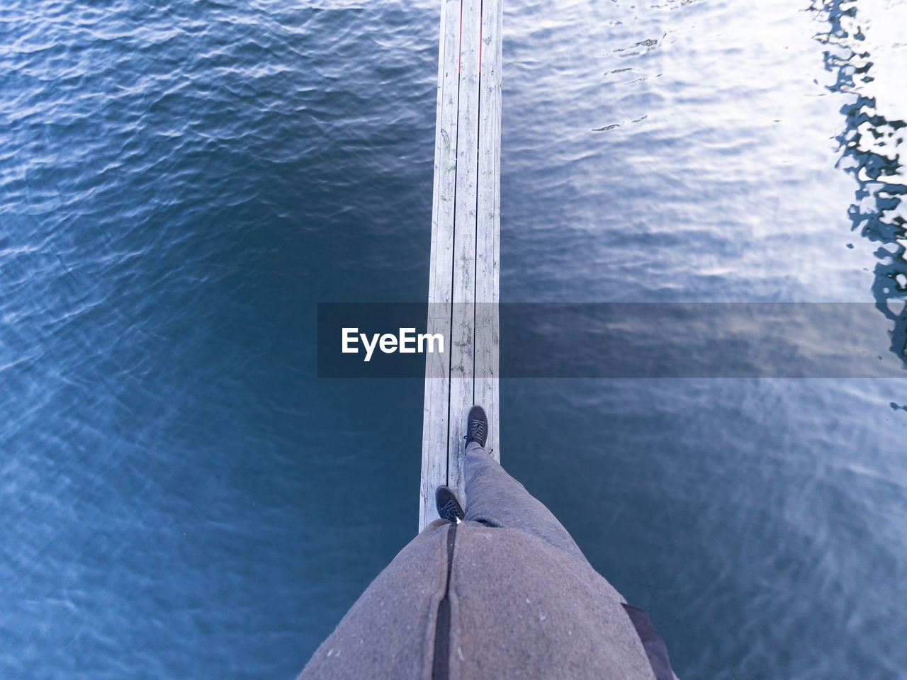 High angle view of man balancing on beam over water