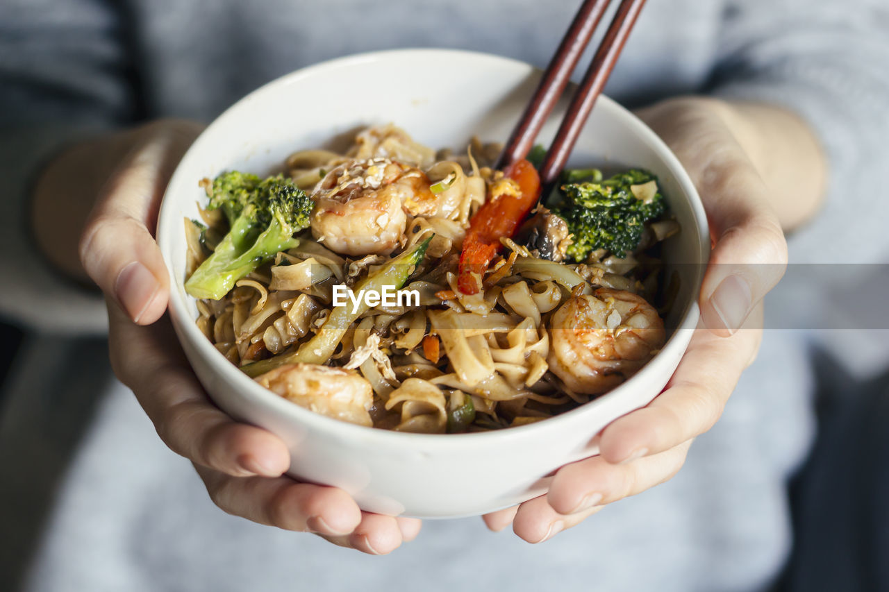 MIDSECTION OF PERSON HOLDING BOWL WITH NOODLES