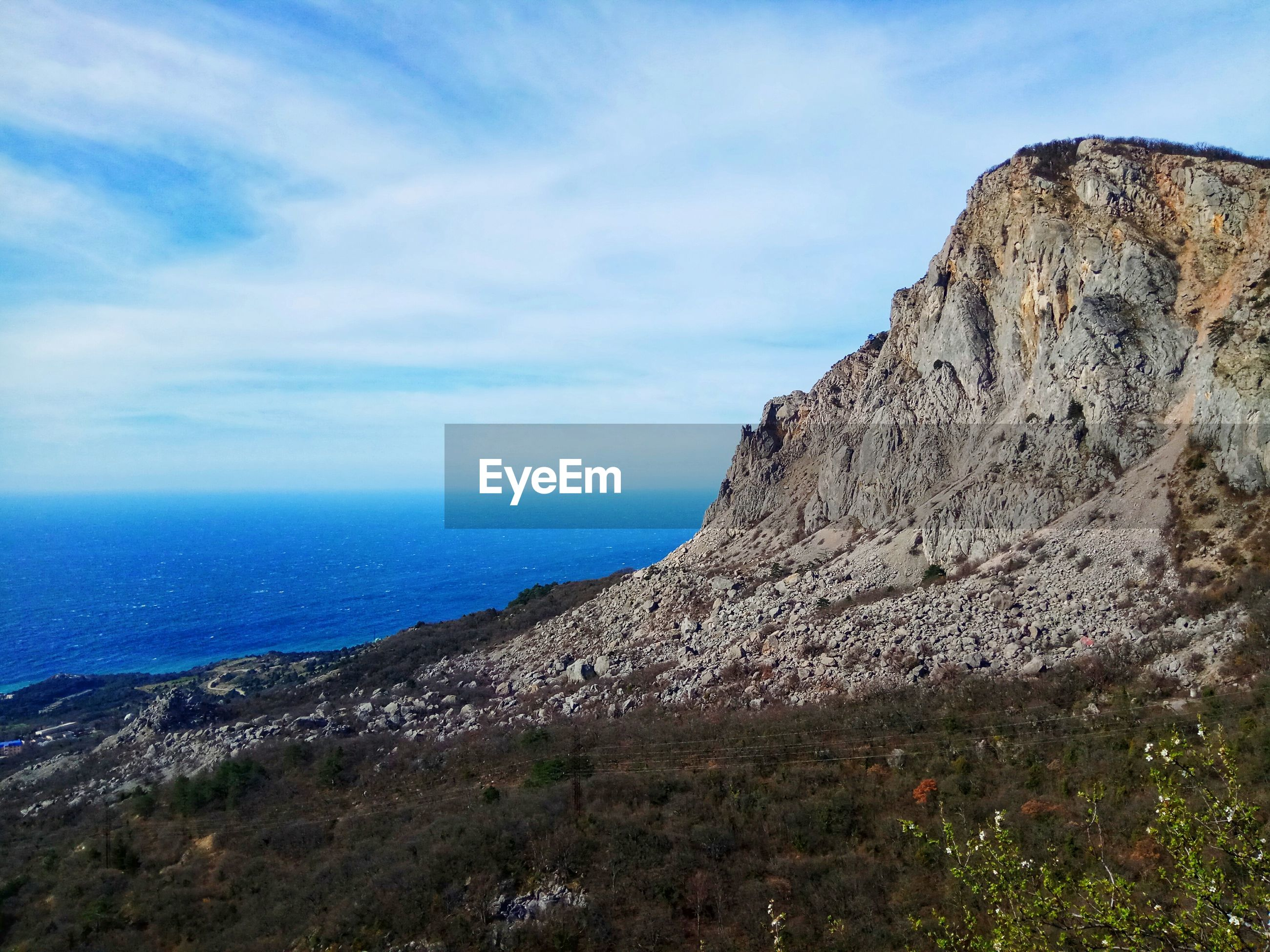 SCENIC VIEW OF SEA BY ROCK FORMATION AGAINST SKY