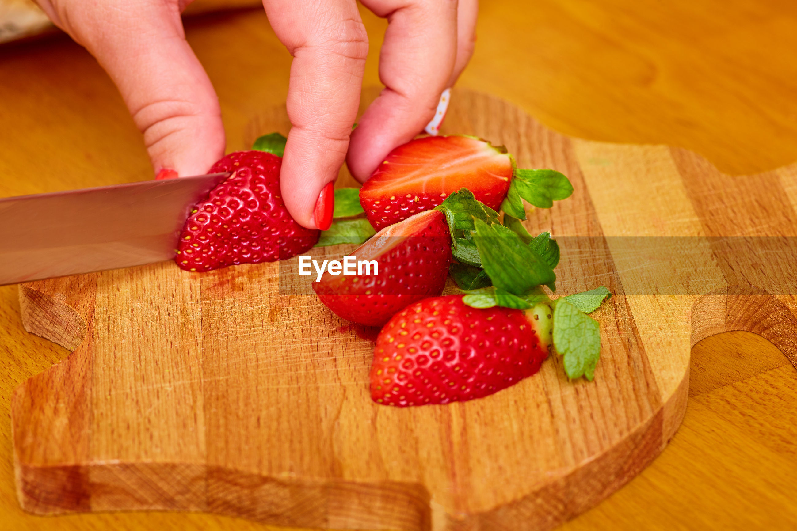HIGH ANGLE VIEW OF WOMAN HOLDING STRAWBERRIES IN CUTTING BOARD