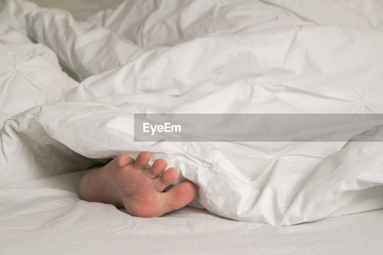Low Section Of Woman Lying Down In Blanket On Bed