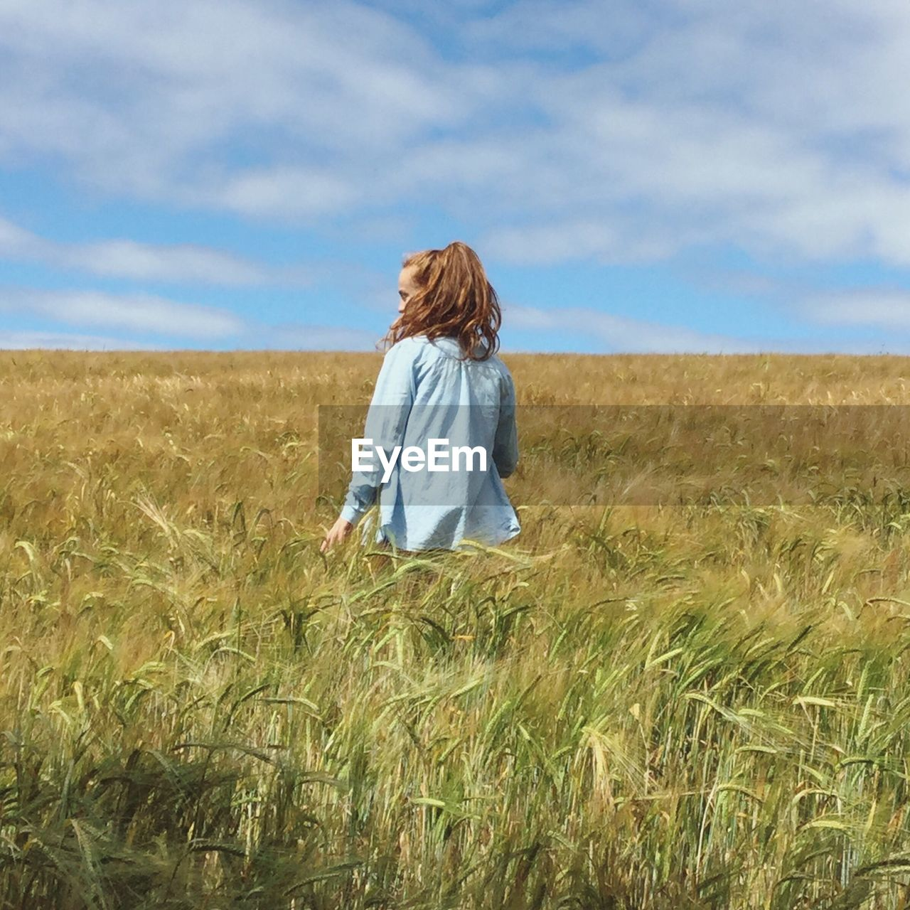 Rear View Of Woman Standing On Wheat Field Against Sky