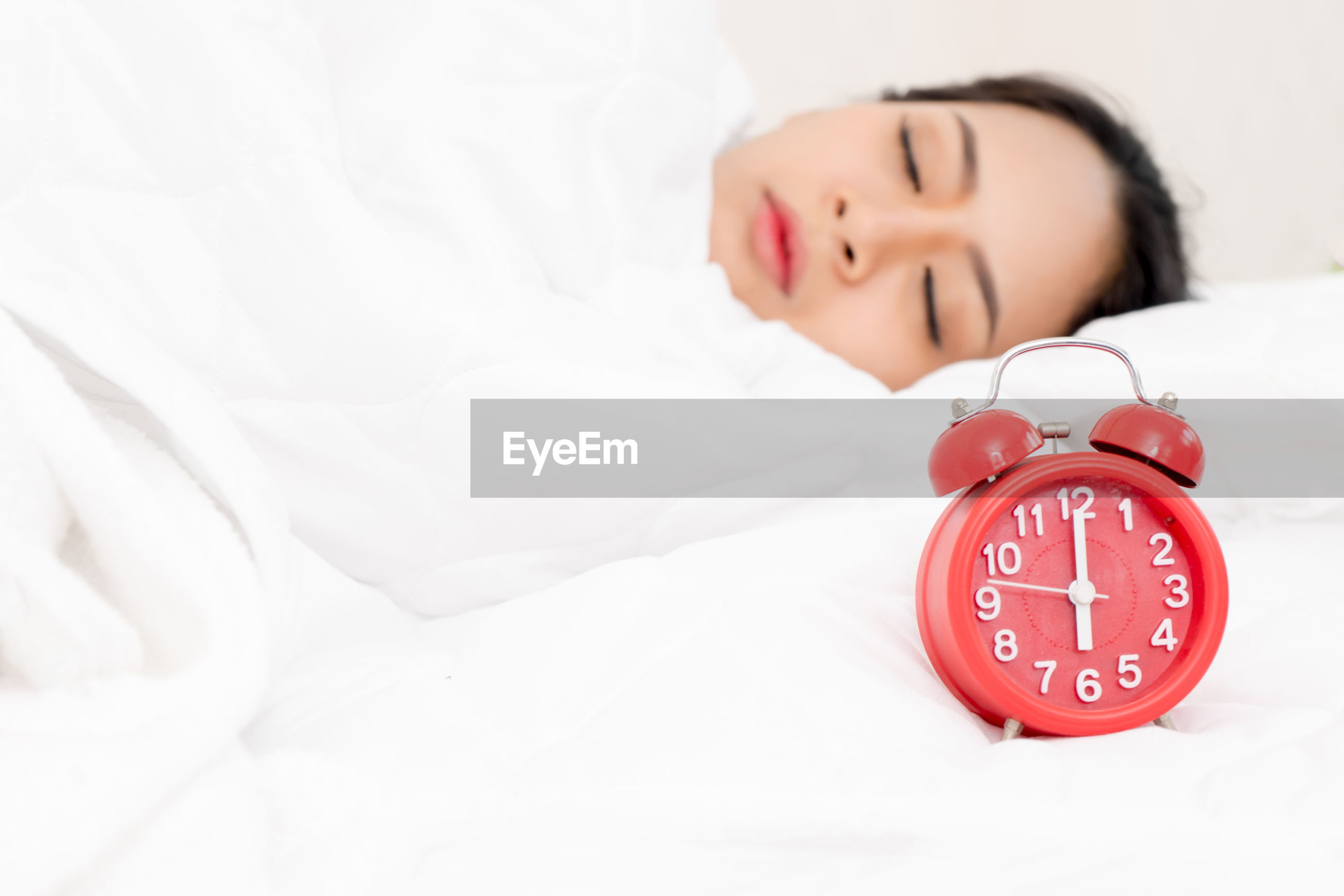 Woman sleeping with alarm clock on bed