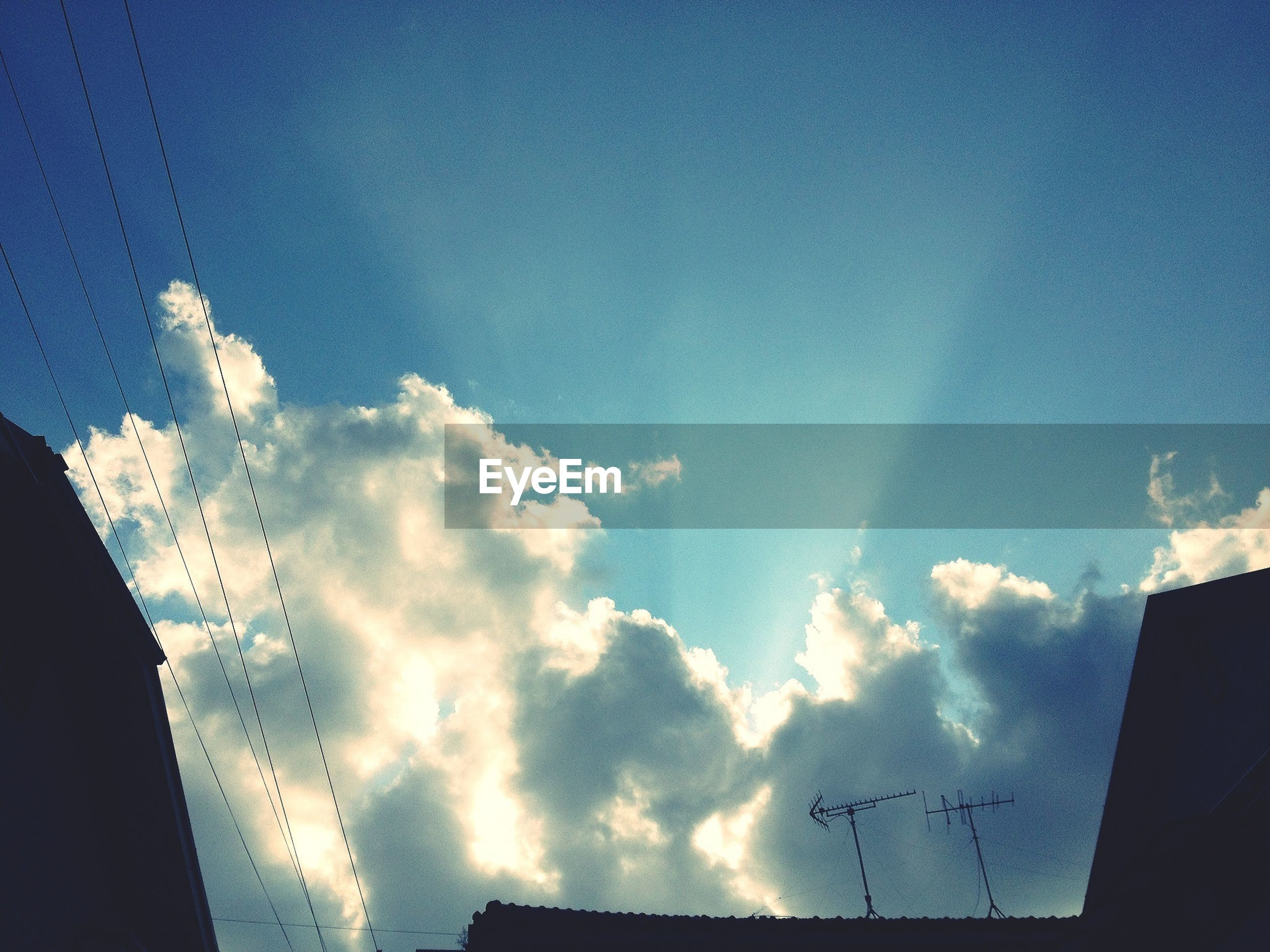 low angle view, sky, blue, cloud - sky, building exterior, built structure, silhouette, architecture, cloud, high section, nature, outdoors, cloudy, power line, no people, day, beauty in nature, dusk, building, house