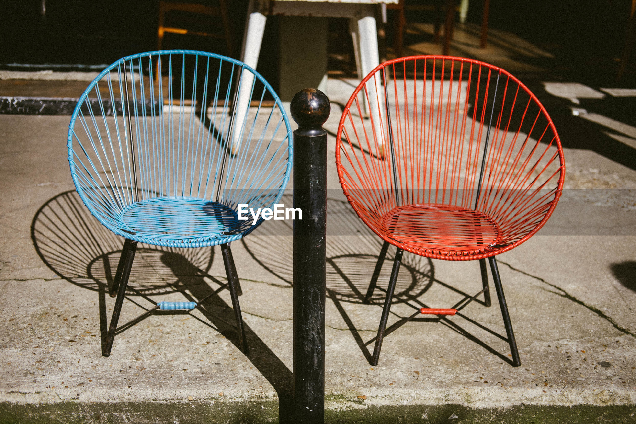 EMPTY CHAIRS AND TABLE BY SIDEWALK CAFE