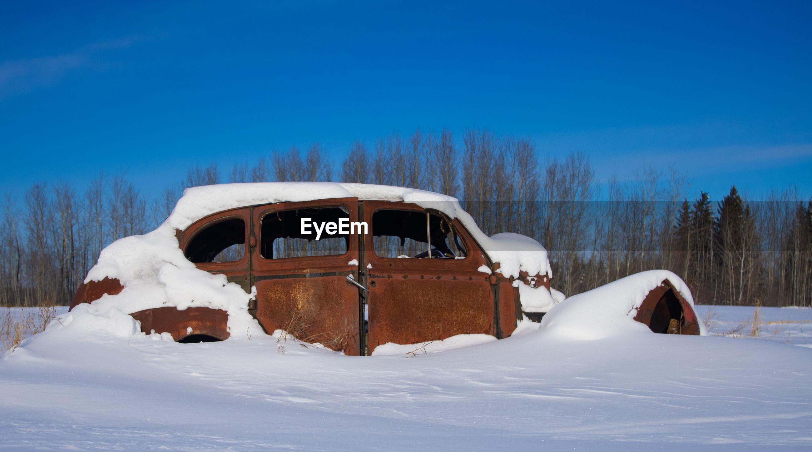 SNOW COVERED CAR ON LAND AGAINST SKY