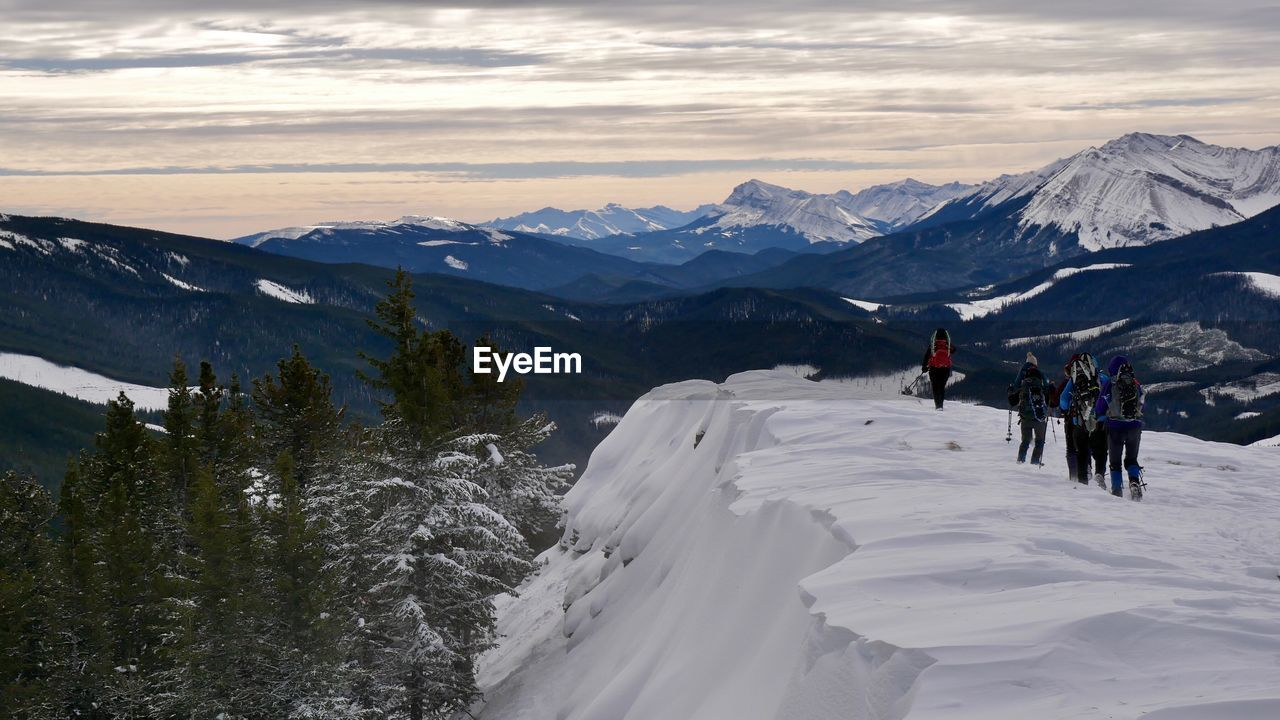 High angle view of people walking on snow covered mountain