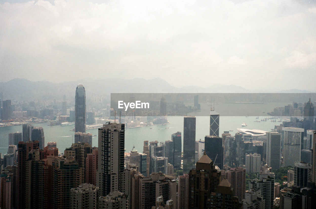 Cityscape At Victoria Harbour Against Sky During Foggy Weather