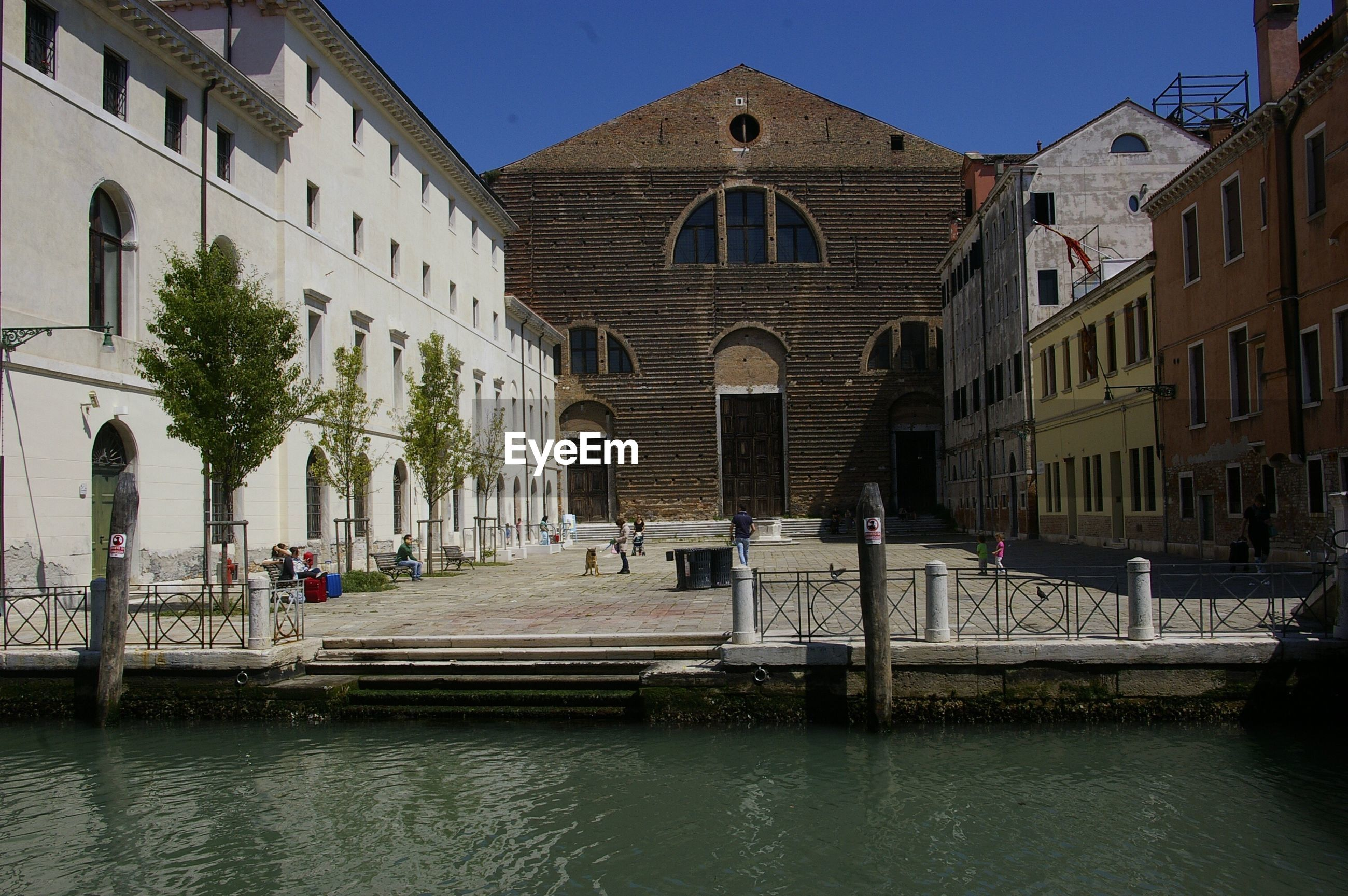building exterior, built structure, architecture, waterfront, clear sky, water, in front of, canal, day, outdoors, sky, facade, town, city life, famous place, tourism, local landmark, place of worship, old town, history