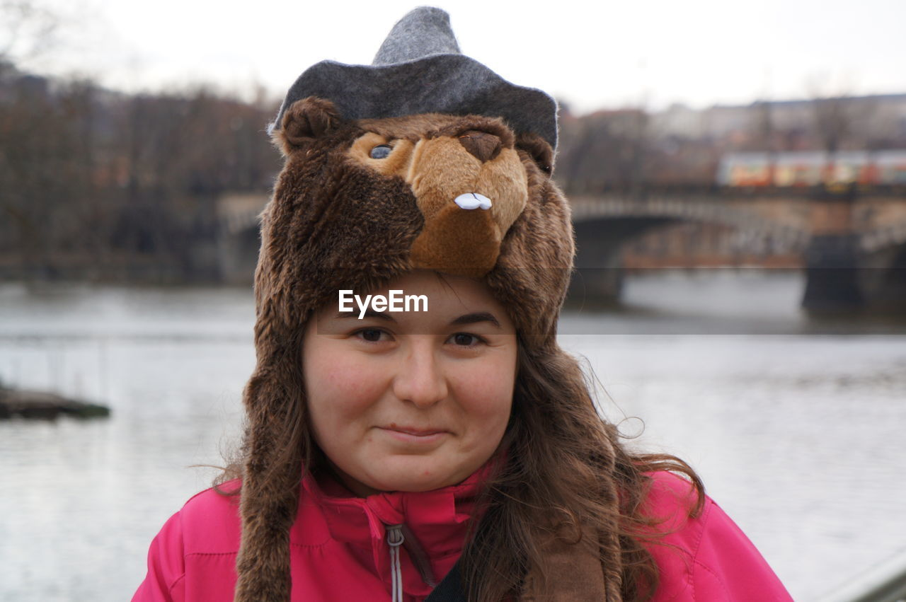 Portrait Of Young Woman Wearing Animal Hat Against River