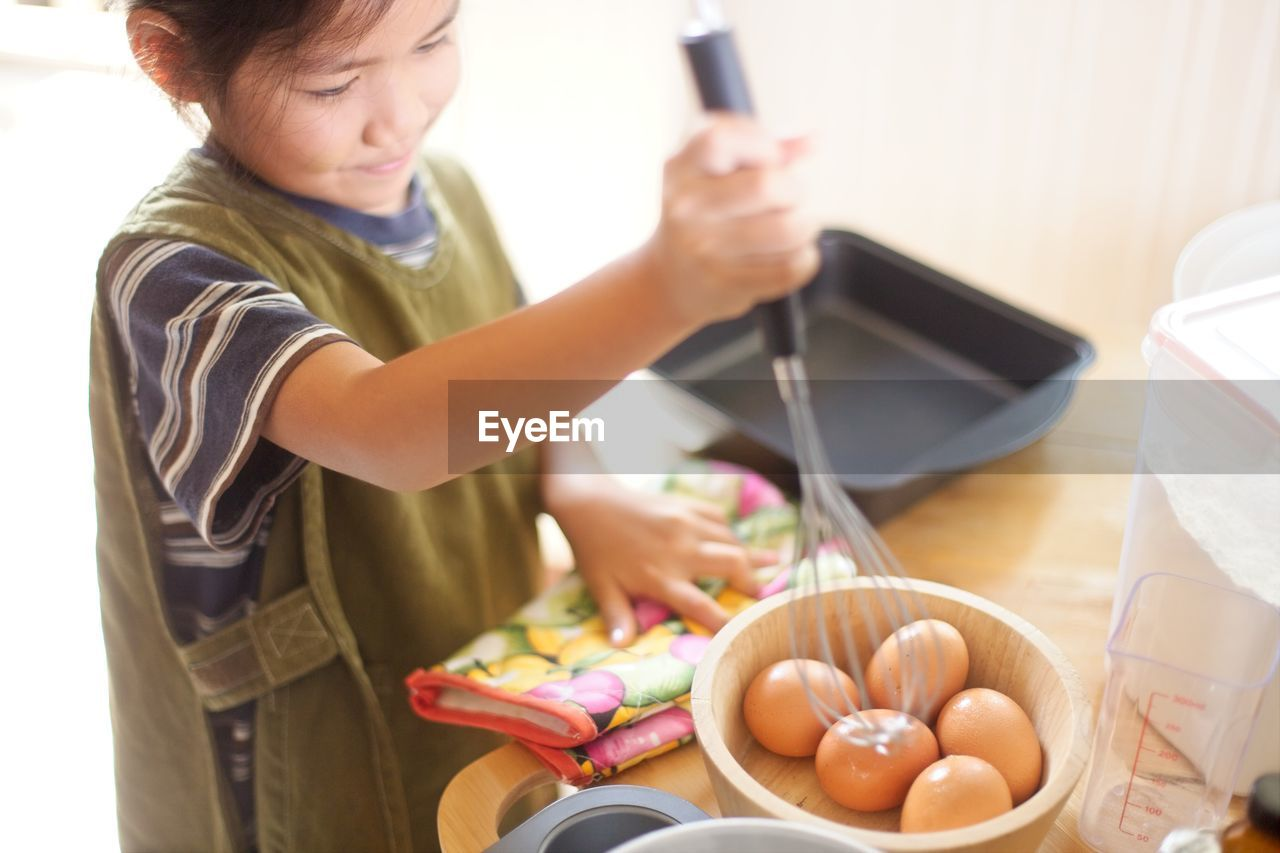 High angle view of girl preparing food in kitchen
