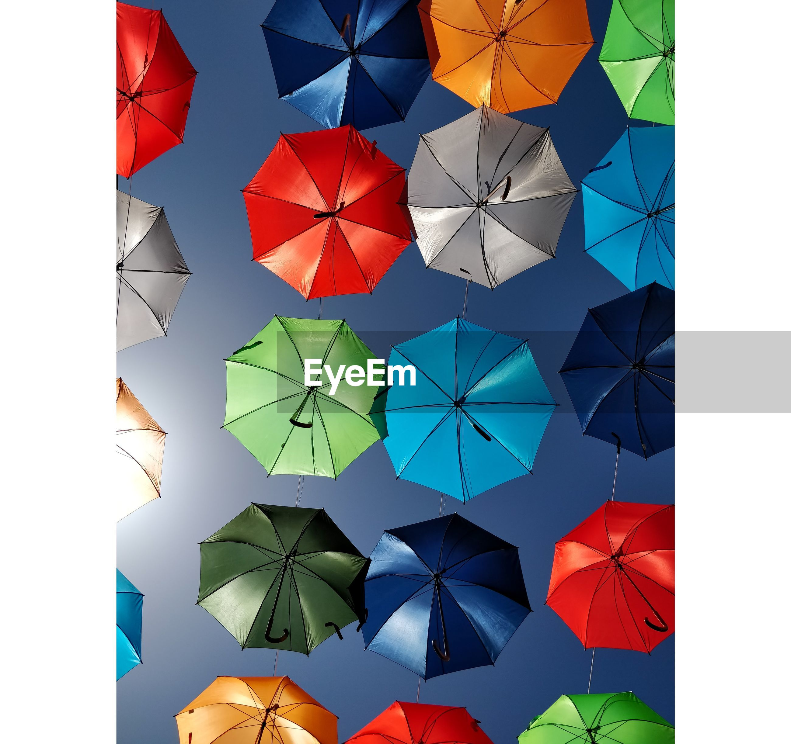 Directly below shot of colorful umbrellas hanging against clear sky