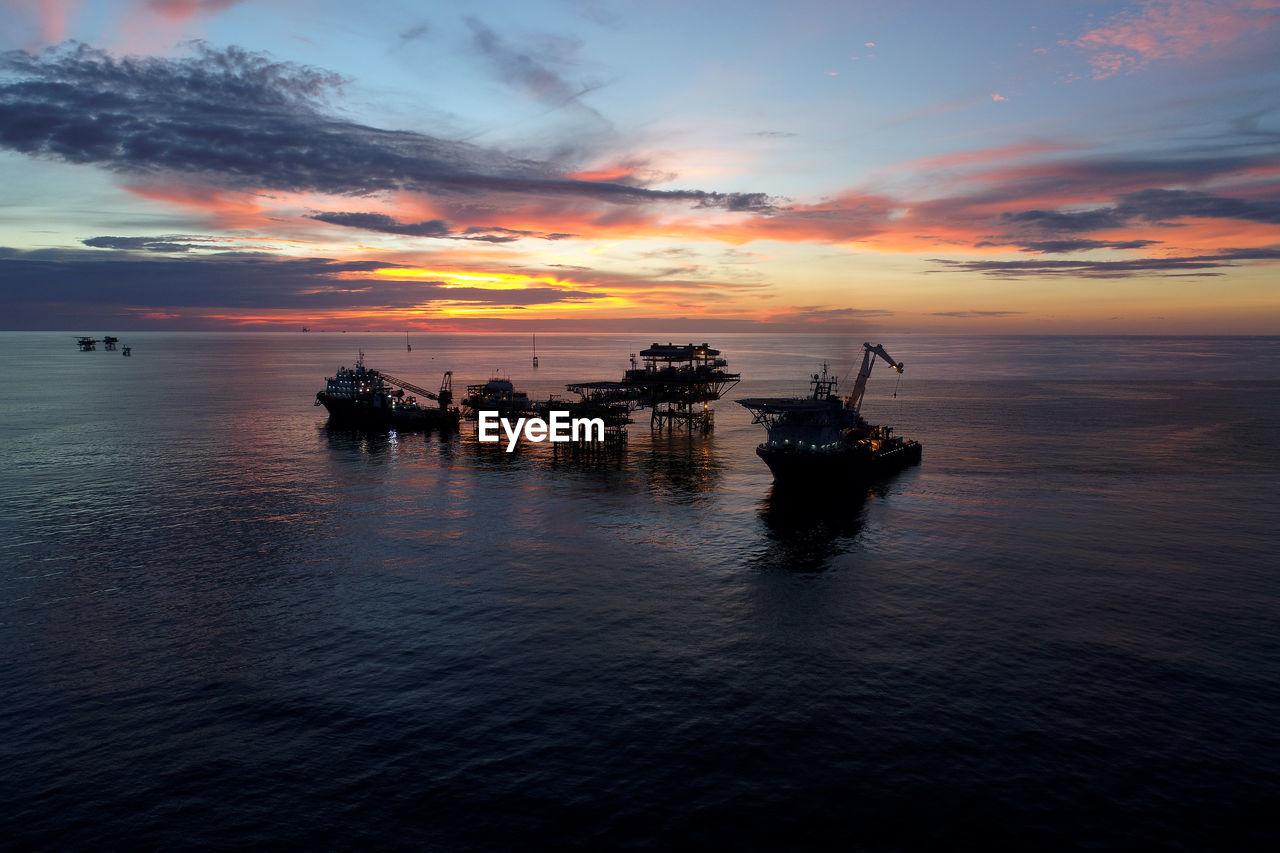 Offshore platform on sea during sunset