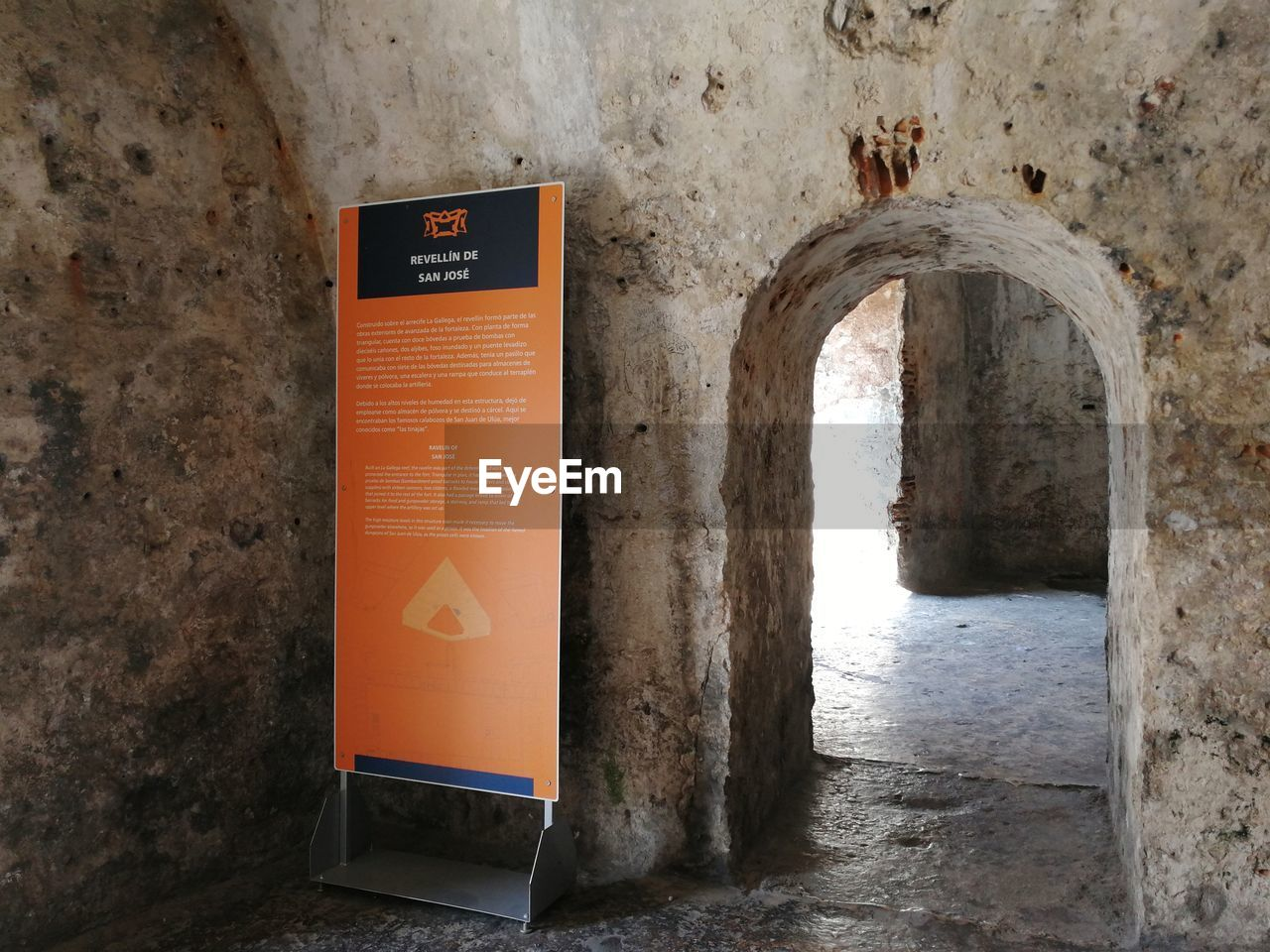 communication, text, architecture, no people, sign, wall - building feature, built structure, western script, indoors, day, orange color, arch, entrance, safety, door, building, protection, security, nature