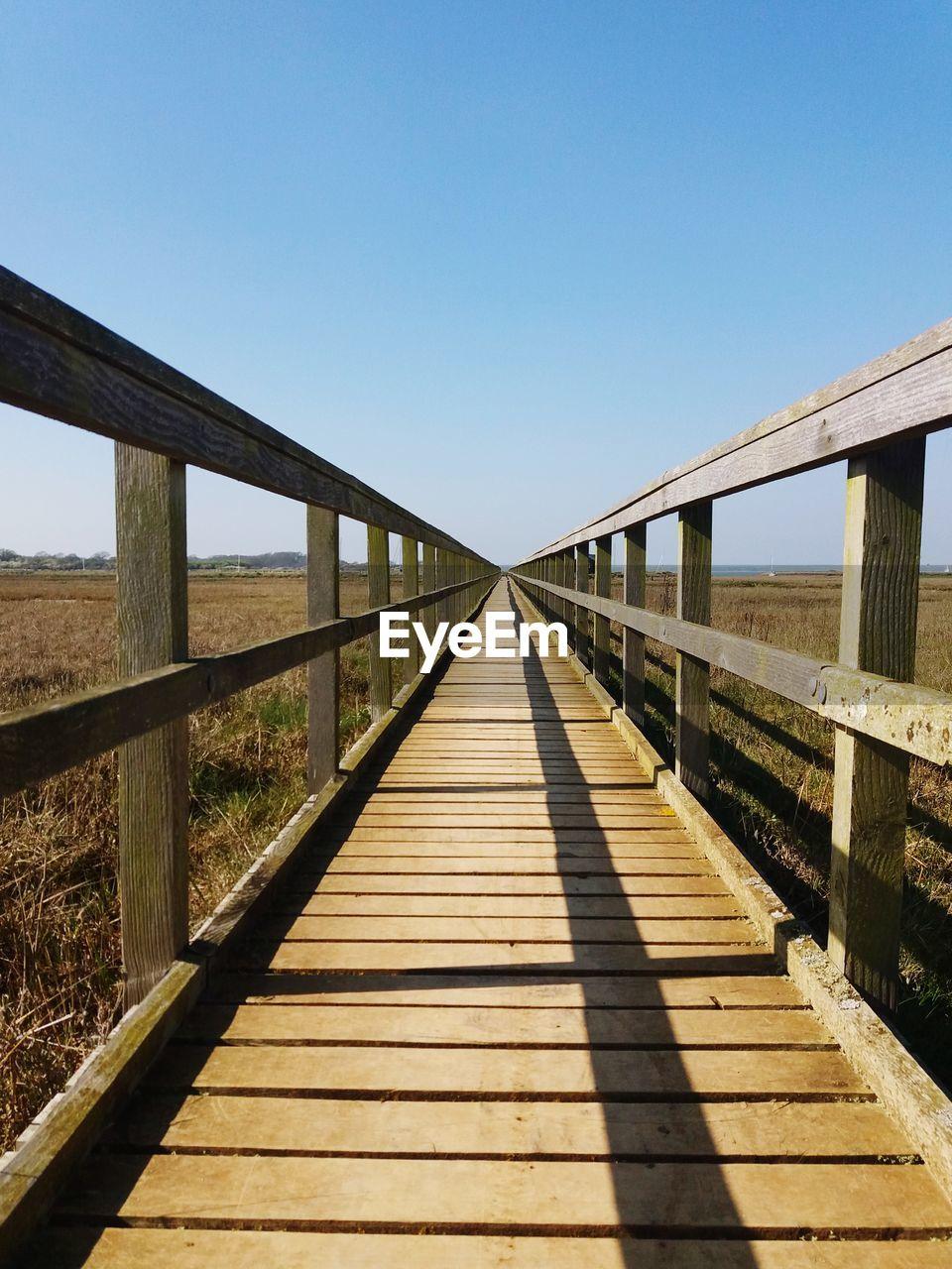 Footbridge amidst landscape against sky