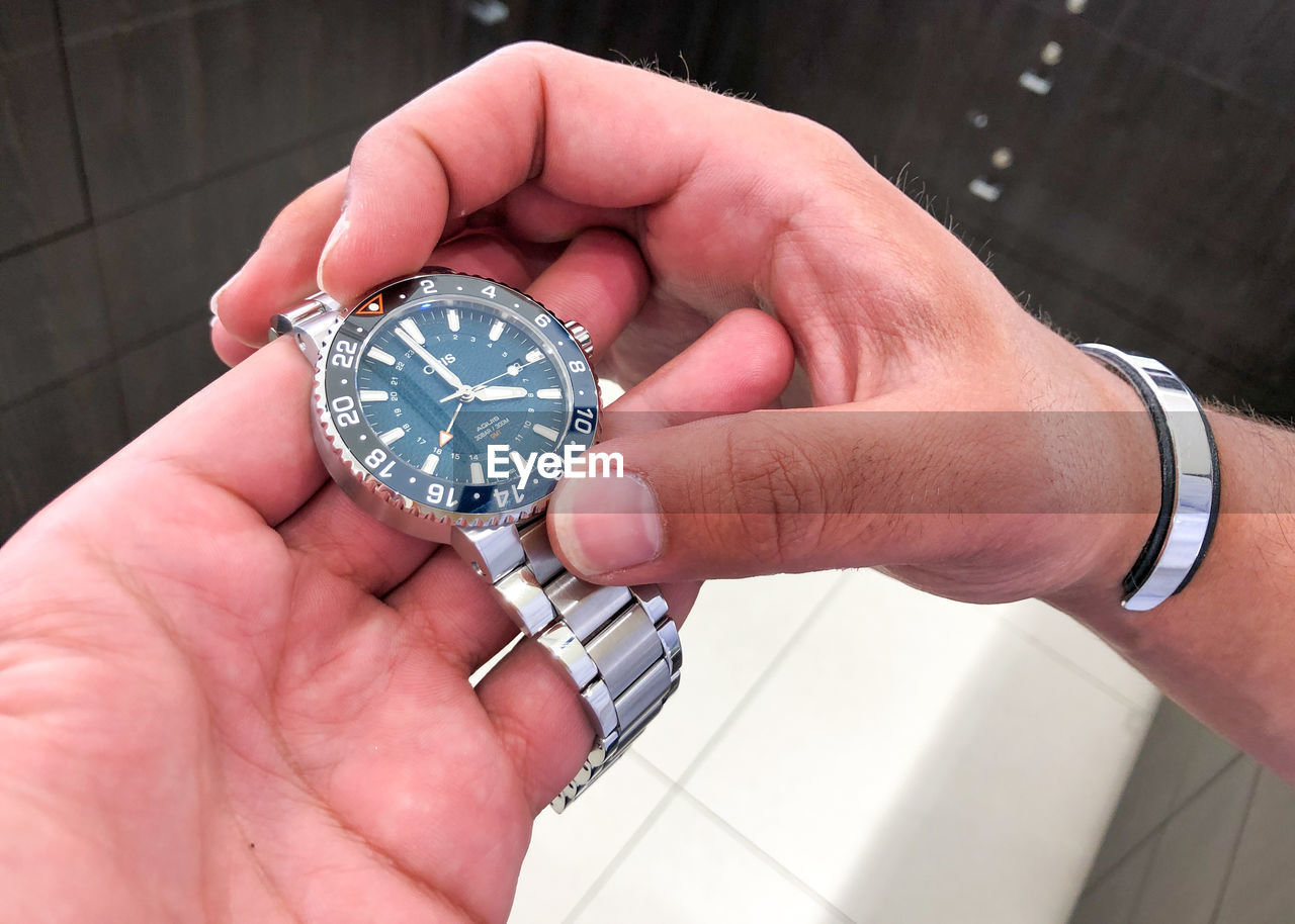 HIGH ANGLE VIEW OF PERSON HOLDING CLOCK