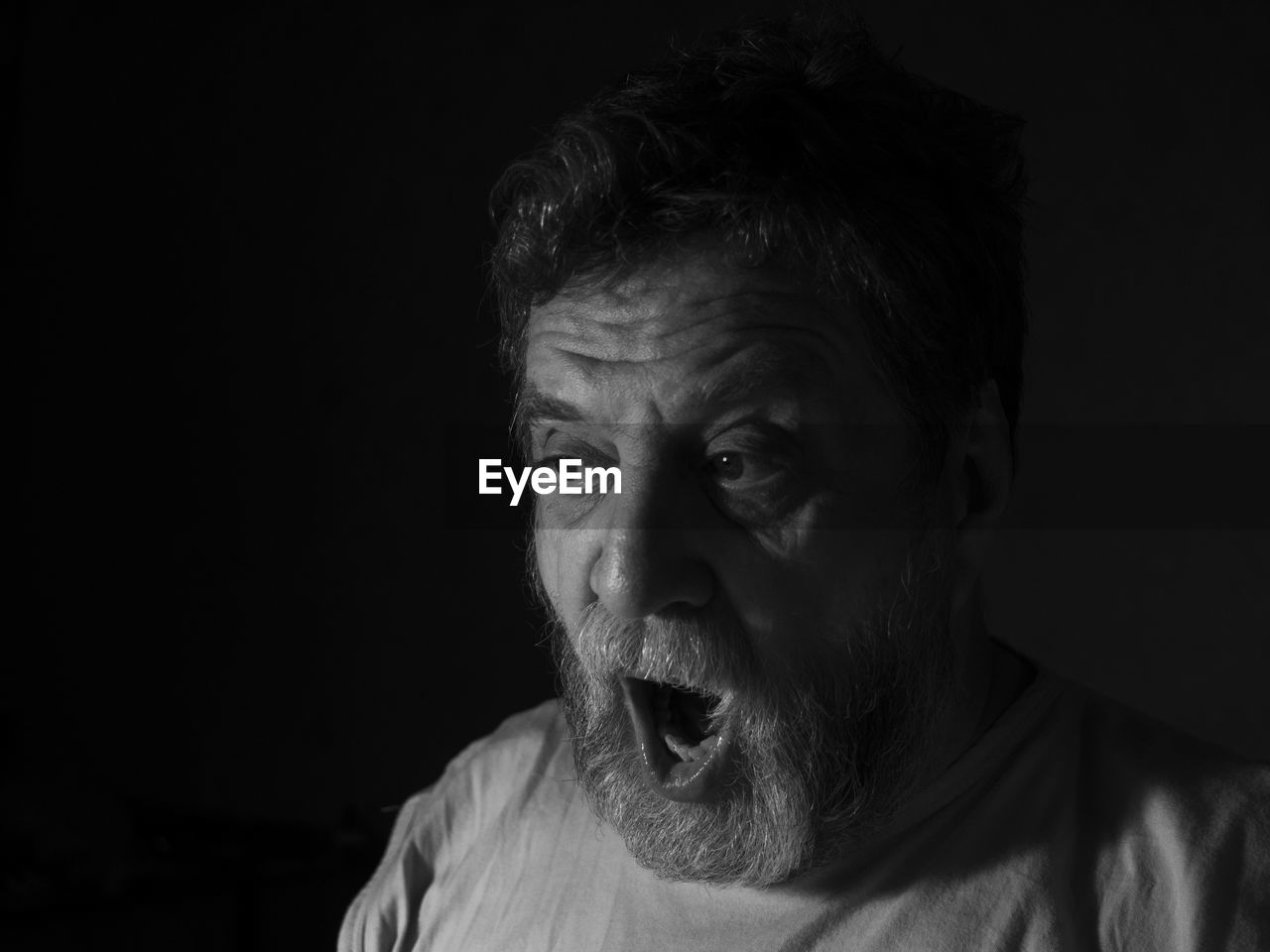 Close-Up Portrait Of Surprised Man Against Black Background