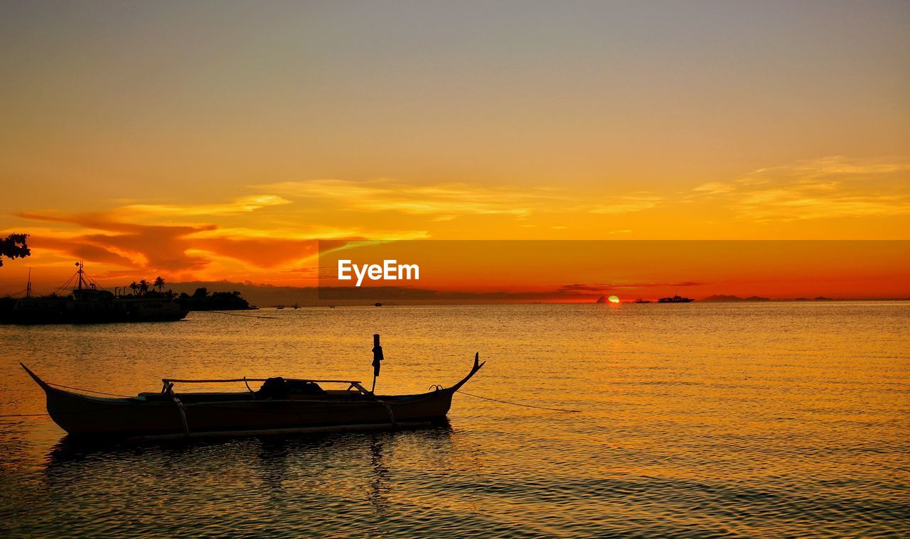 sunset, orange color, nautical vessel, water, transportation, silhouette, sea, beauty in nature, nature, sky, mode of transport, scenics, outdoors, waterfront, horizon over water, longtail boat, no people, gondola - traditional boat
