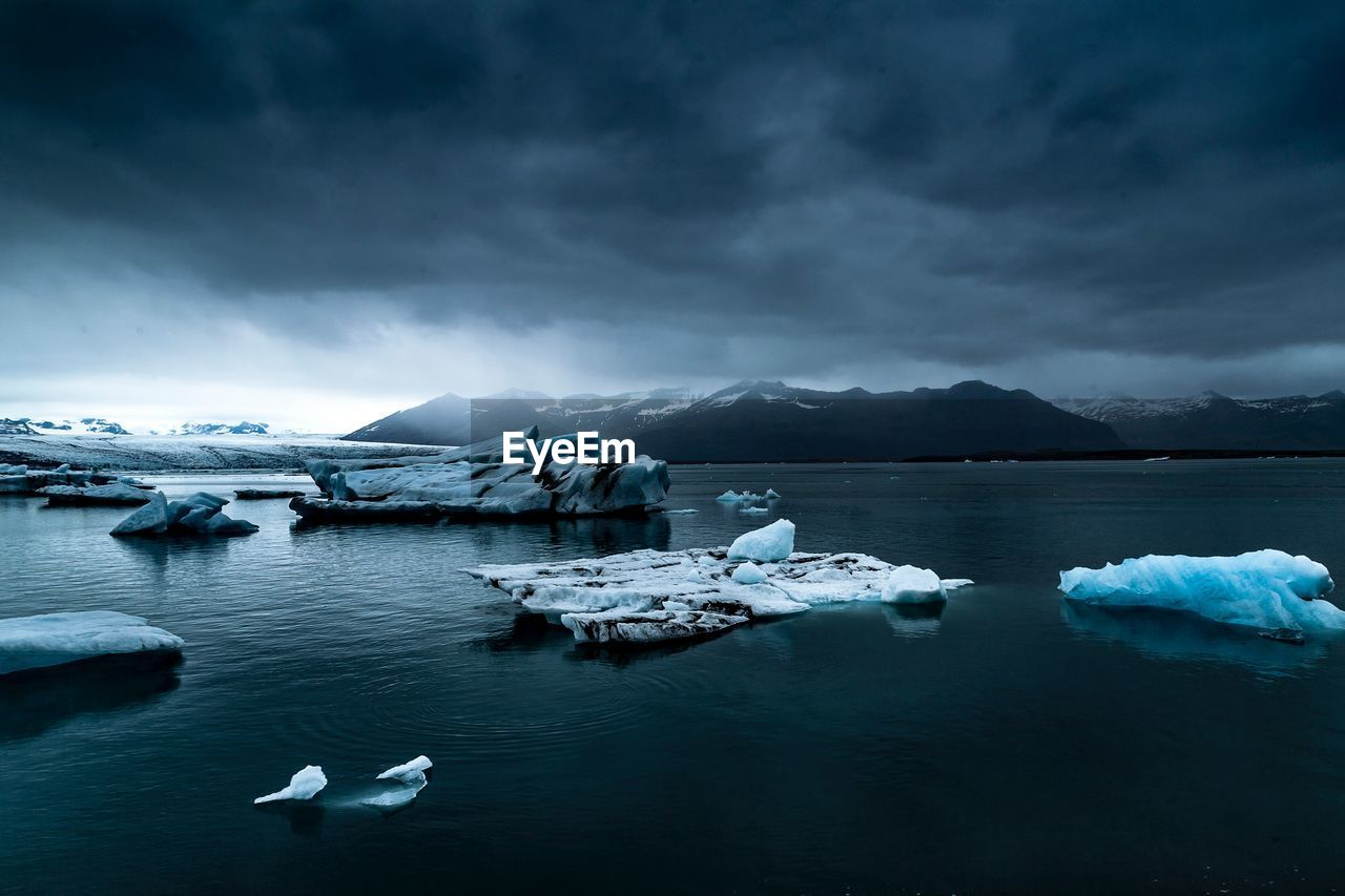 Icebergs Melting In Lake Against Cloudy Sky