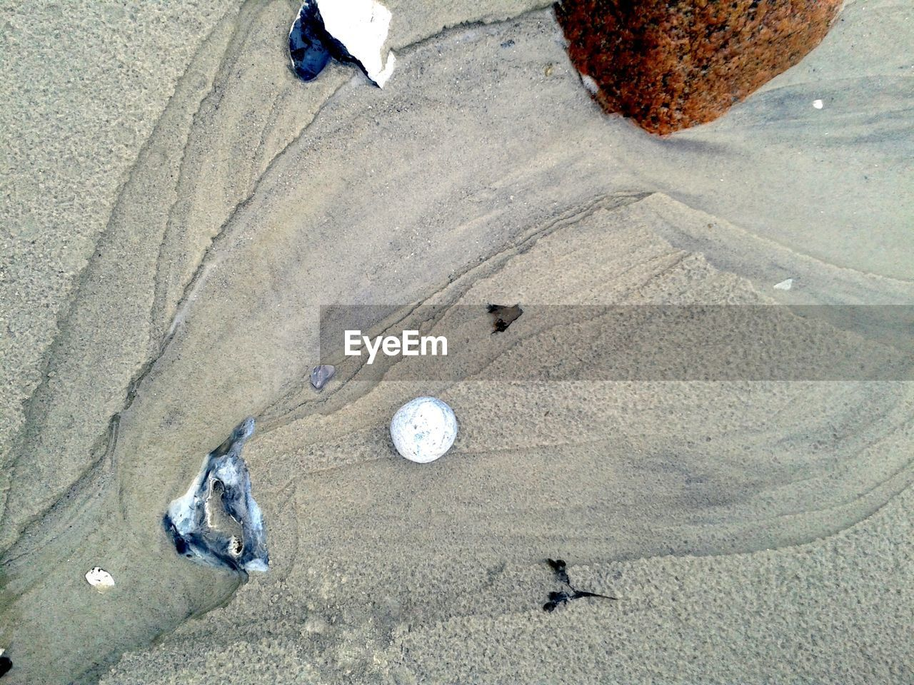 High Angle View Of Rocks On Wet Sand At Beach