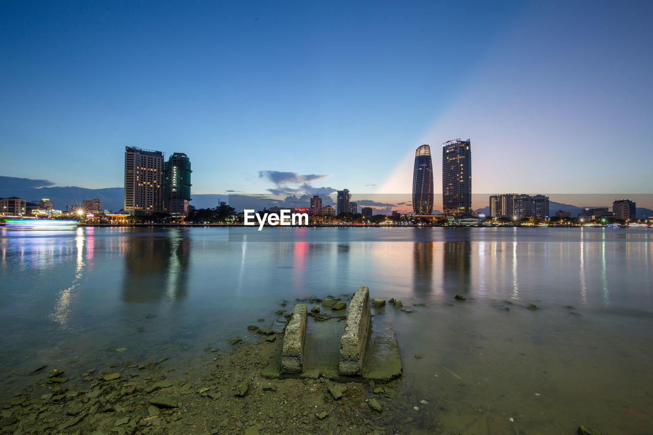 sky, building exterior, architecture, built structure, water, city, building, nature, office building exterior, urban skyline, landscape, skyscraper, illuminated, river, no people, tall - high, office, waterfront, reflection, modern, outdoors, cityscape, bay