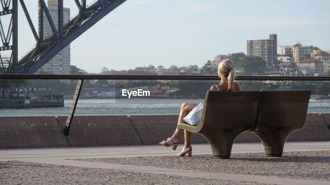 WOMAN SITTING ON BRIDGE AGAINST SKY