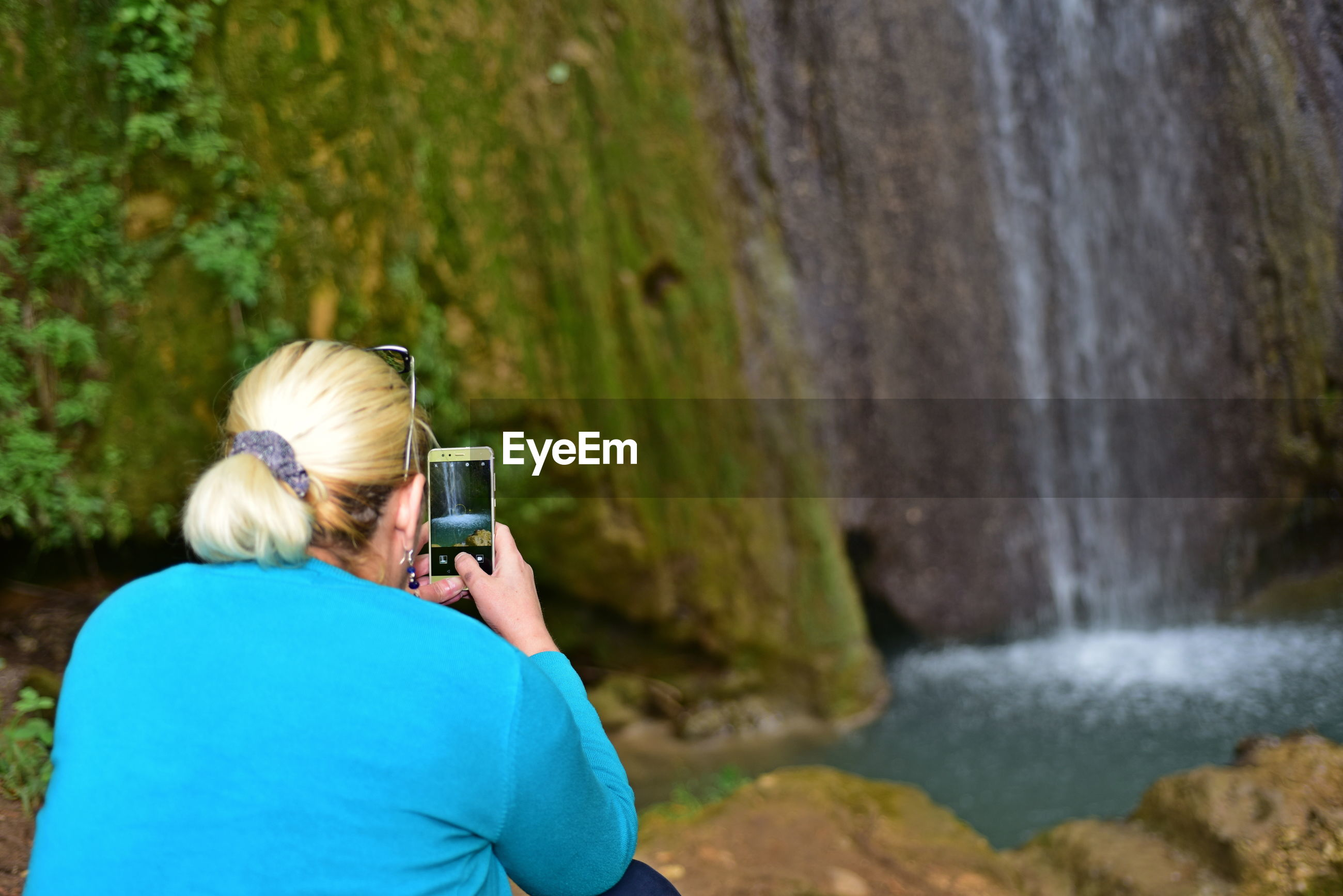 Rear view of woman photographing waterfall with smart phone in forest