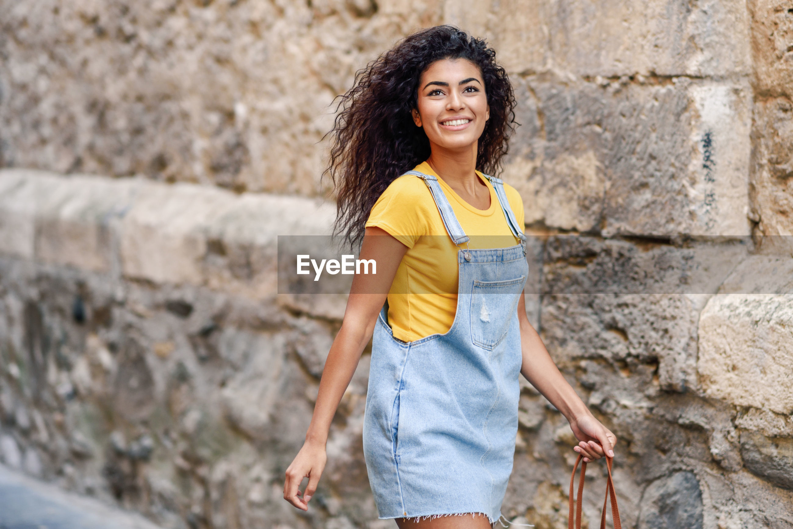 Cheerful young woman looking away while standing against wall