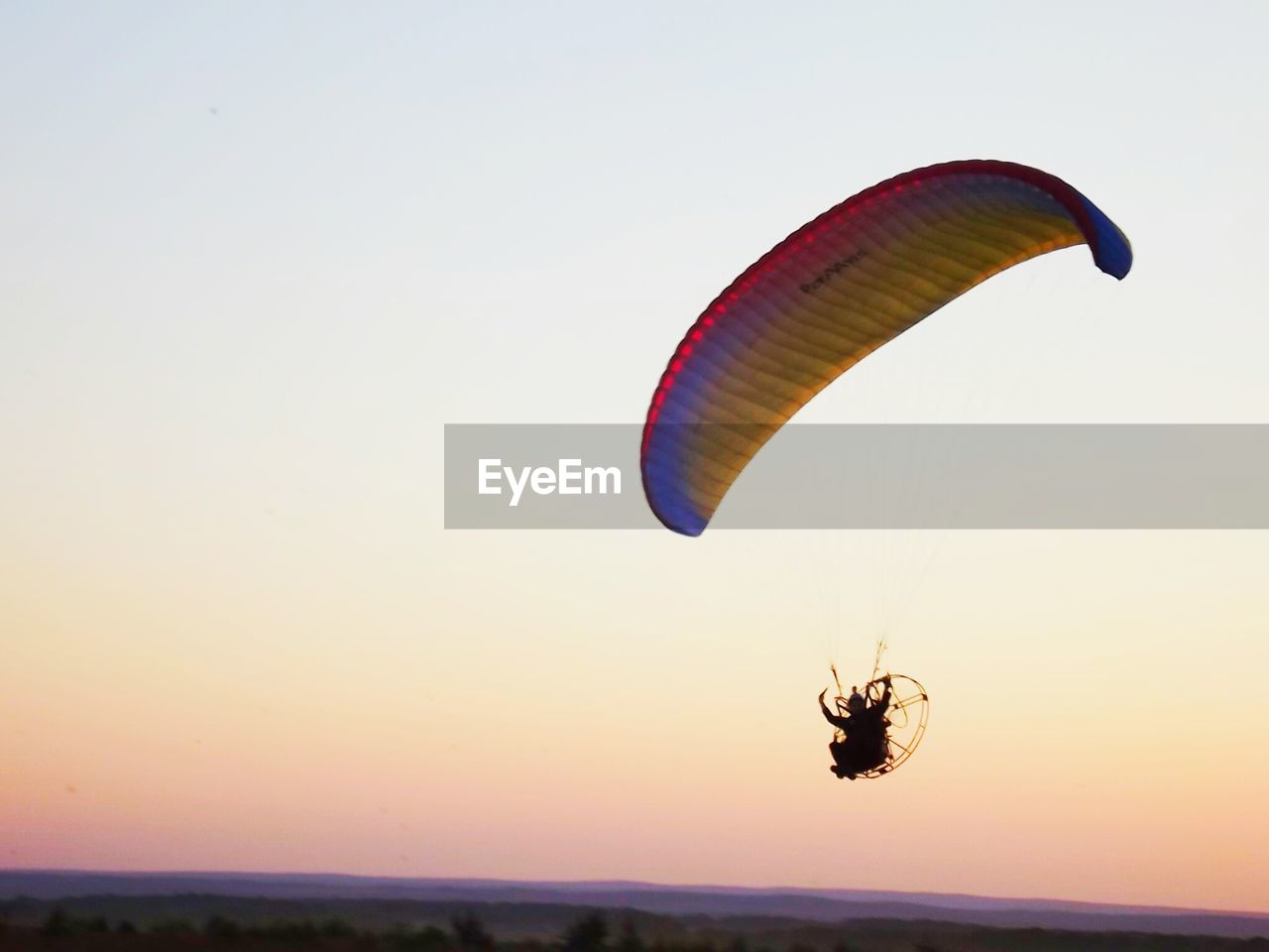 Low angle view of man flying powered parachute against clear sky during sunset