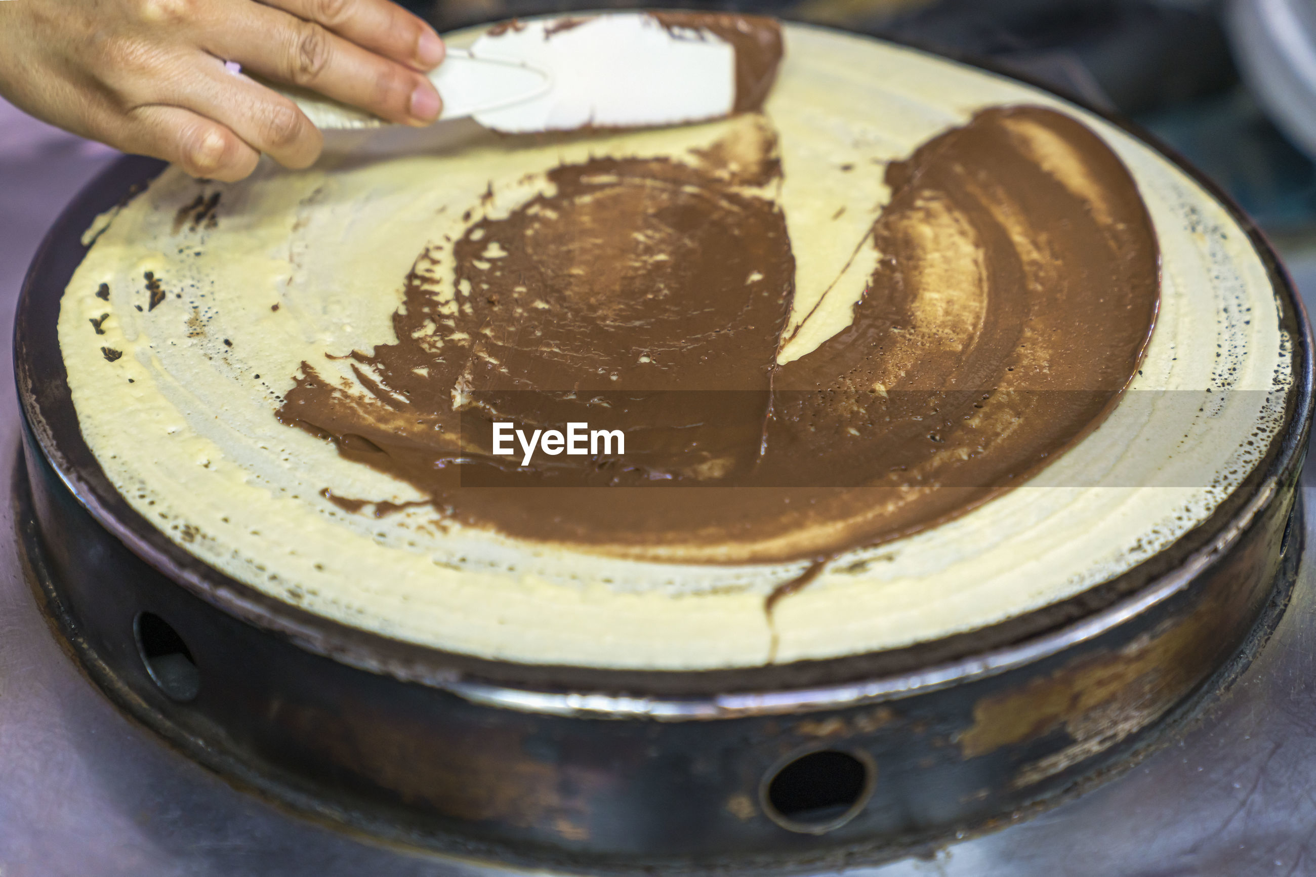 HIGH ANGLE VIEW OF PERSON PREPARING CAKE IN PLATE
