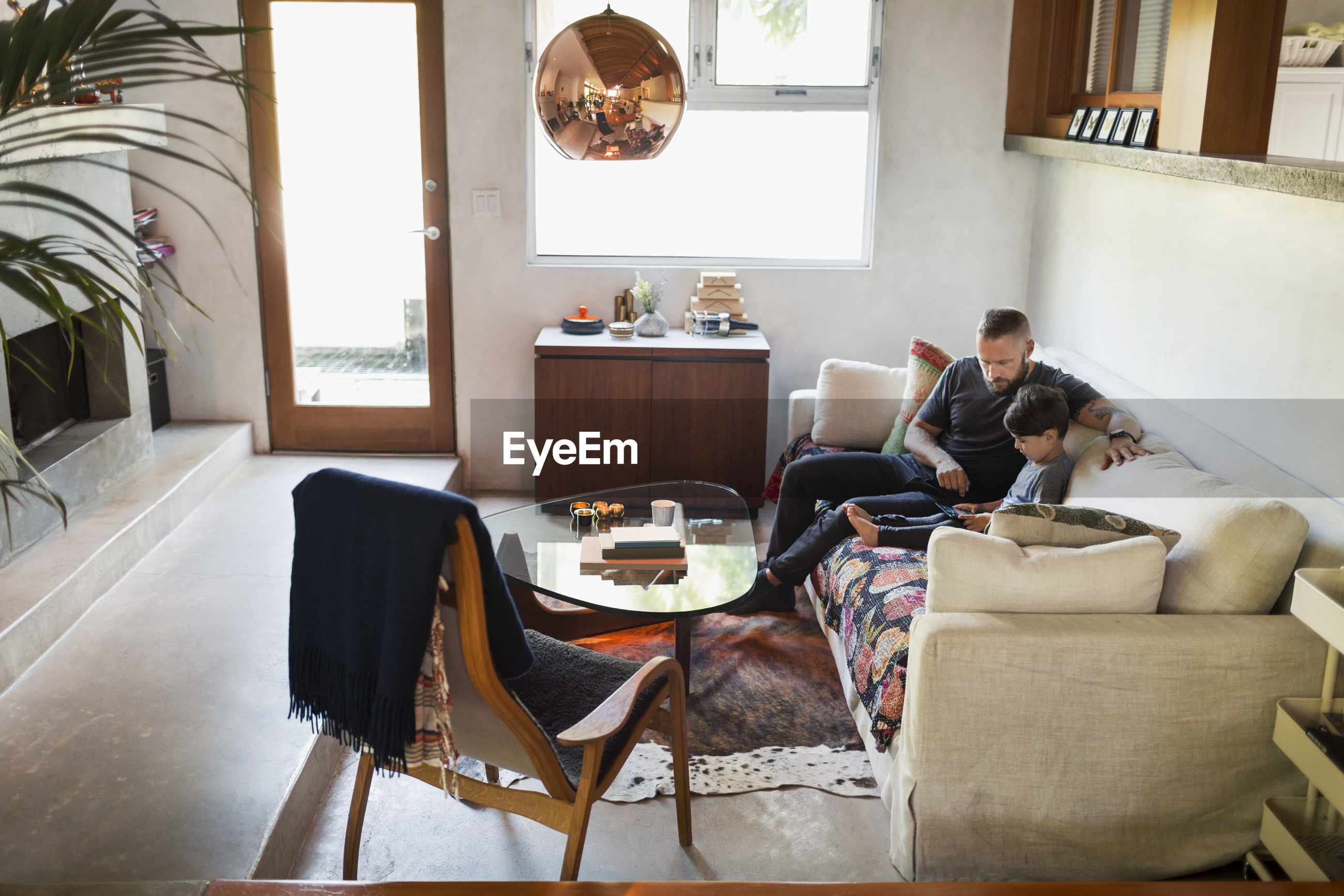 PEOPLE SITTING ON SOFA BY TABLE AT HOME