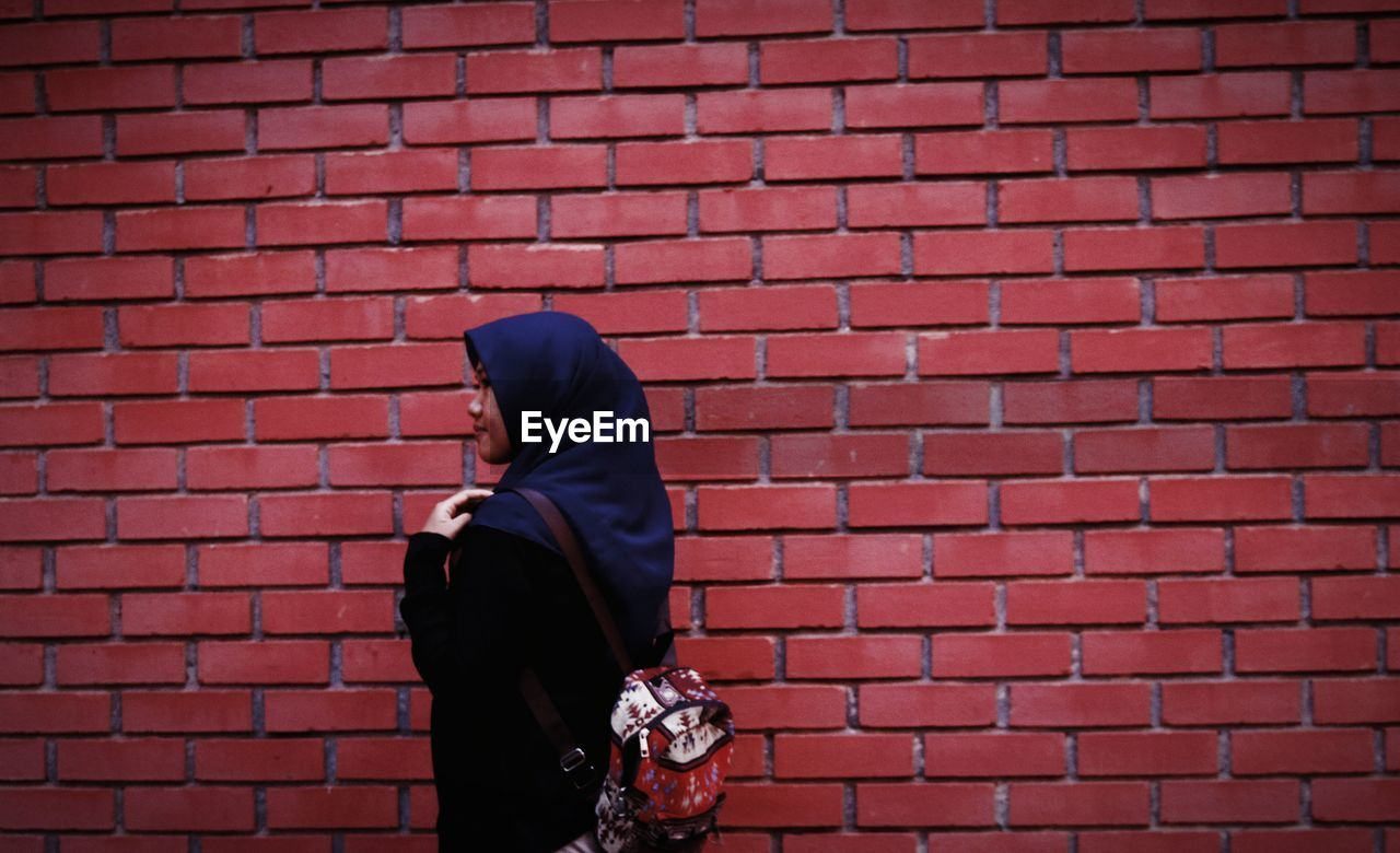 Side view of woman wearing hijab walking by brick wall