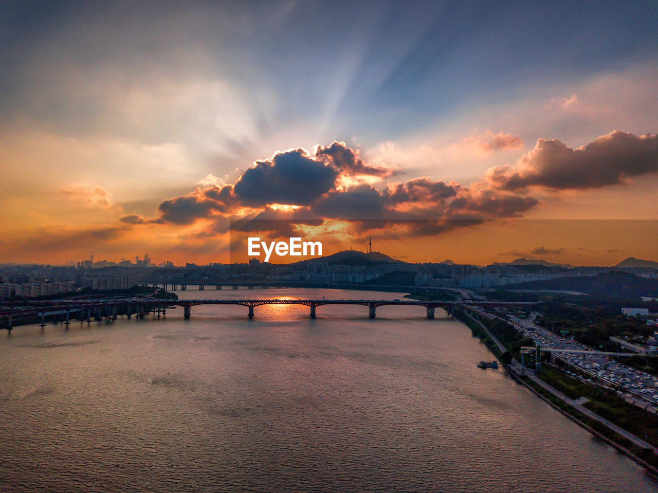 BRIDGE OVER RIVER AGAINST SKY IN CITY DURING SUNSET